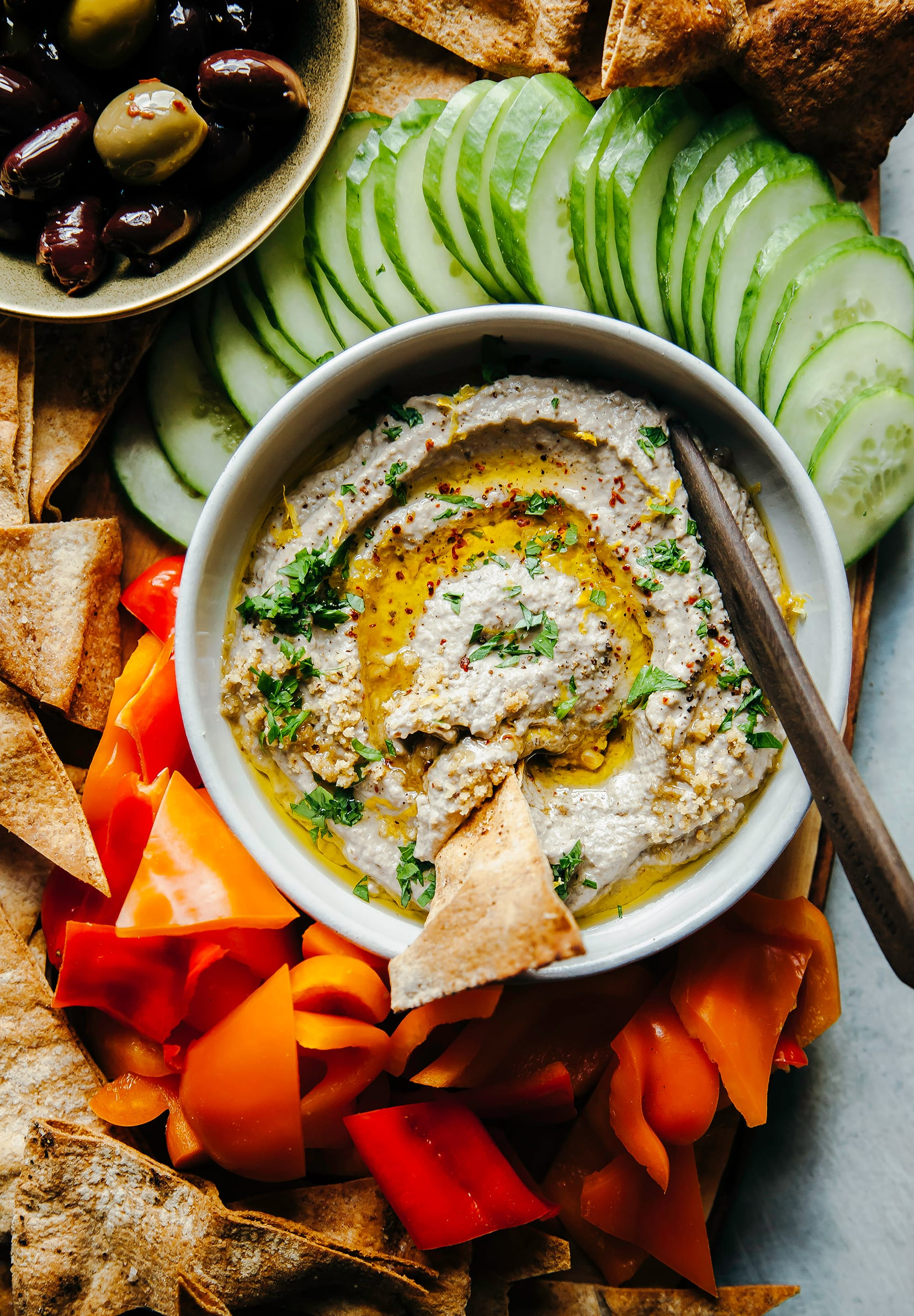 An overhead shot of a creamy beige dip with swirls of olive oil and chopped parsley on top. The bowl of dip is surrounded by pita chips and cut vegetables.