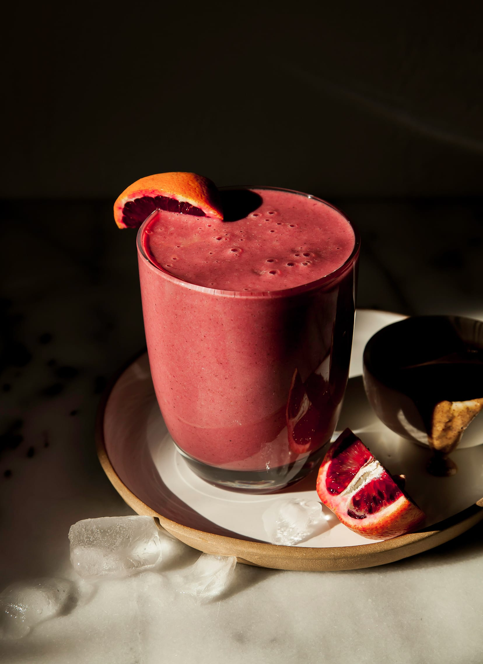 A 3/4 angle shot of a deep burgundy smoothie in a clear glass in harsh sunlight. A sliced blood orange is perched on a plate nearby. Included in a roundup of healthy vegan smoothies.