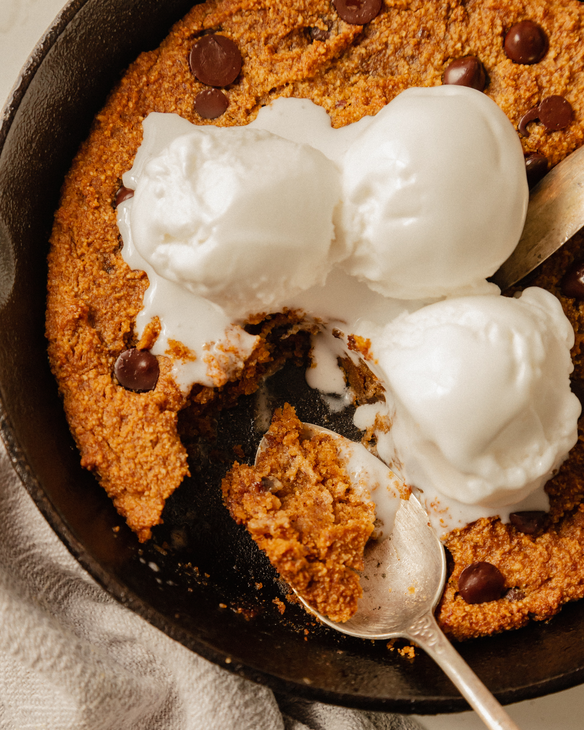 An up close, overhead shot of a slightly orange pumpkin chocolate chip skillet cookie topped with 3 scoops of vanilla ice cream. The ice cream is melt-y and several bites have been taken out of the cookie.