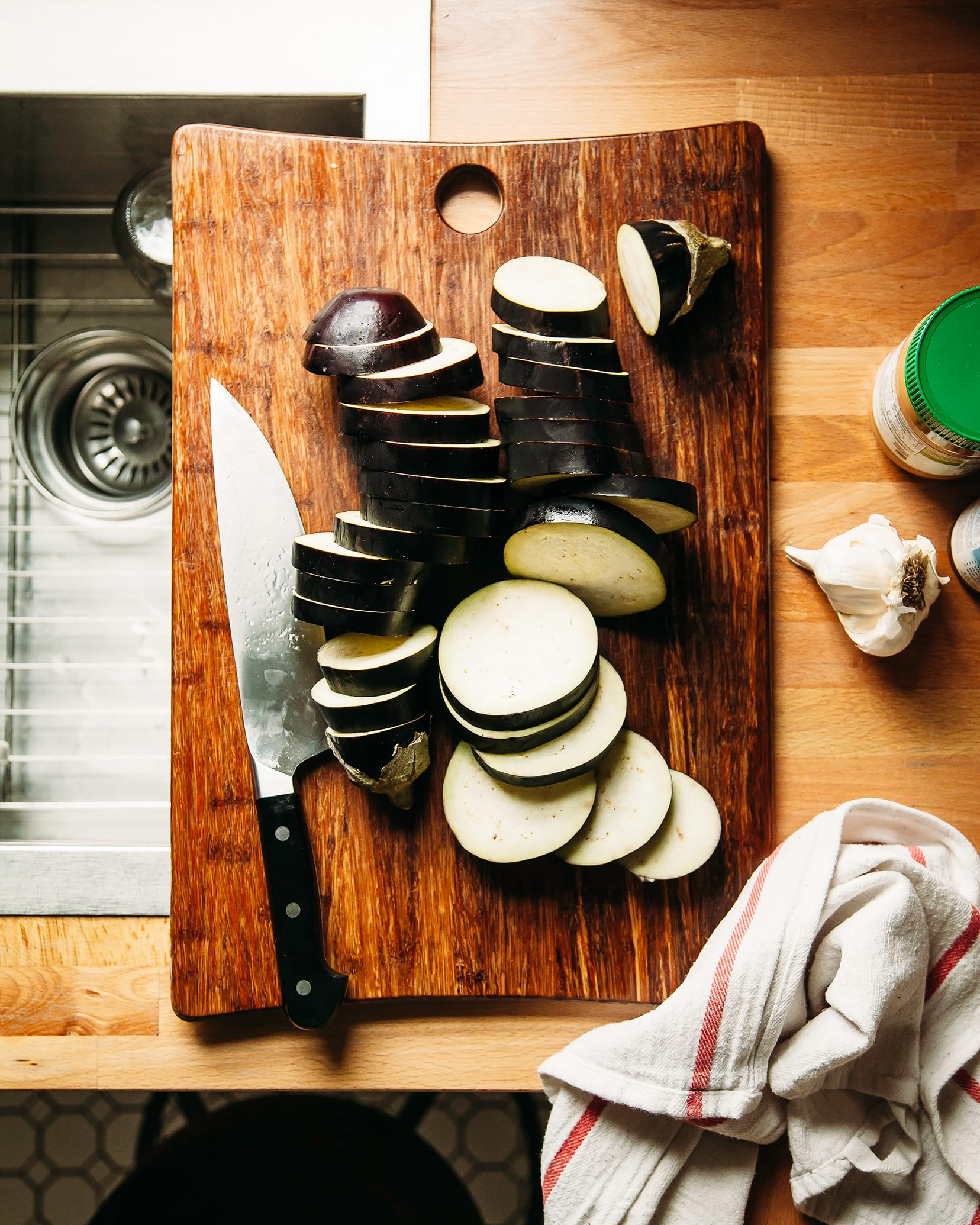 An overhead shot of two sliced eggplants on a wooden cutting board on top of a kitchen counter.