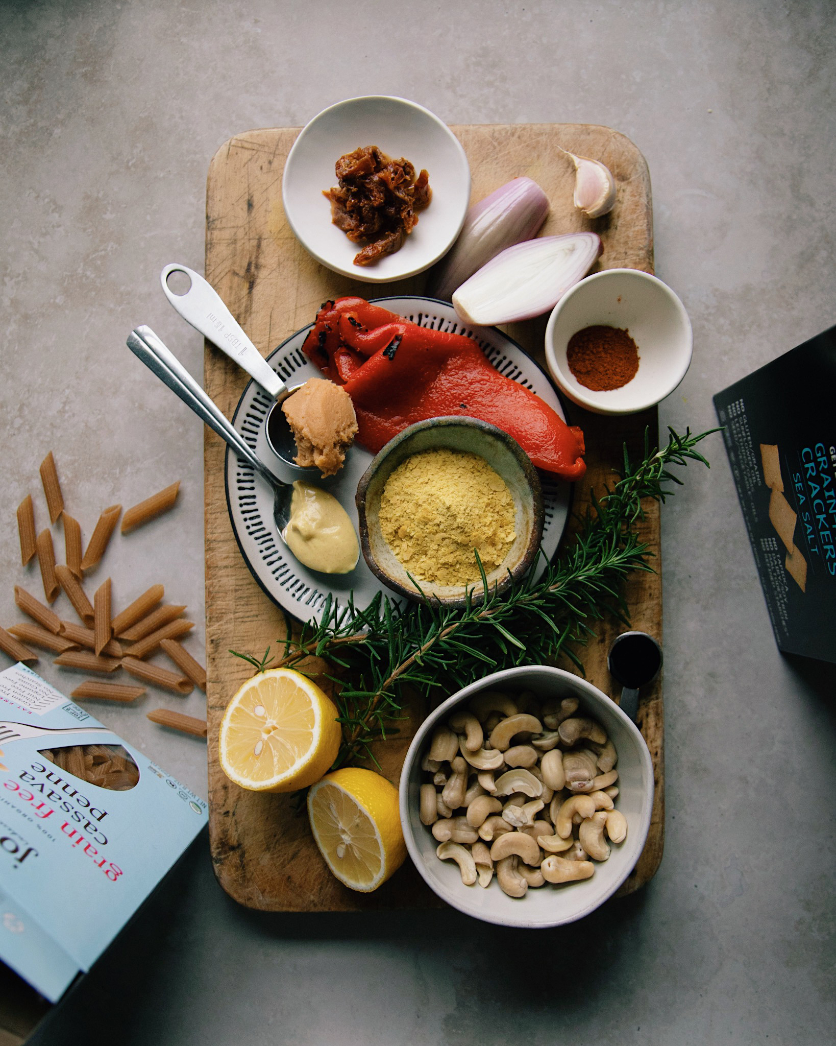 An overhead shot of ingredients on a weathered wood cutting board on top of a grey-beige marbled background.