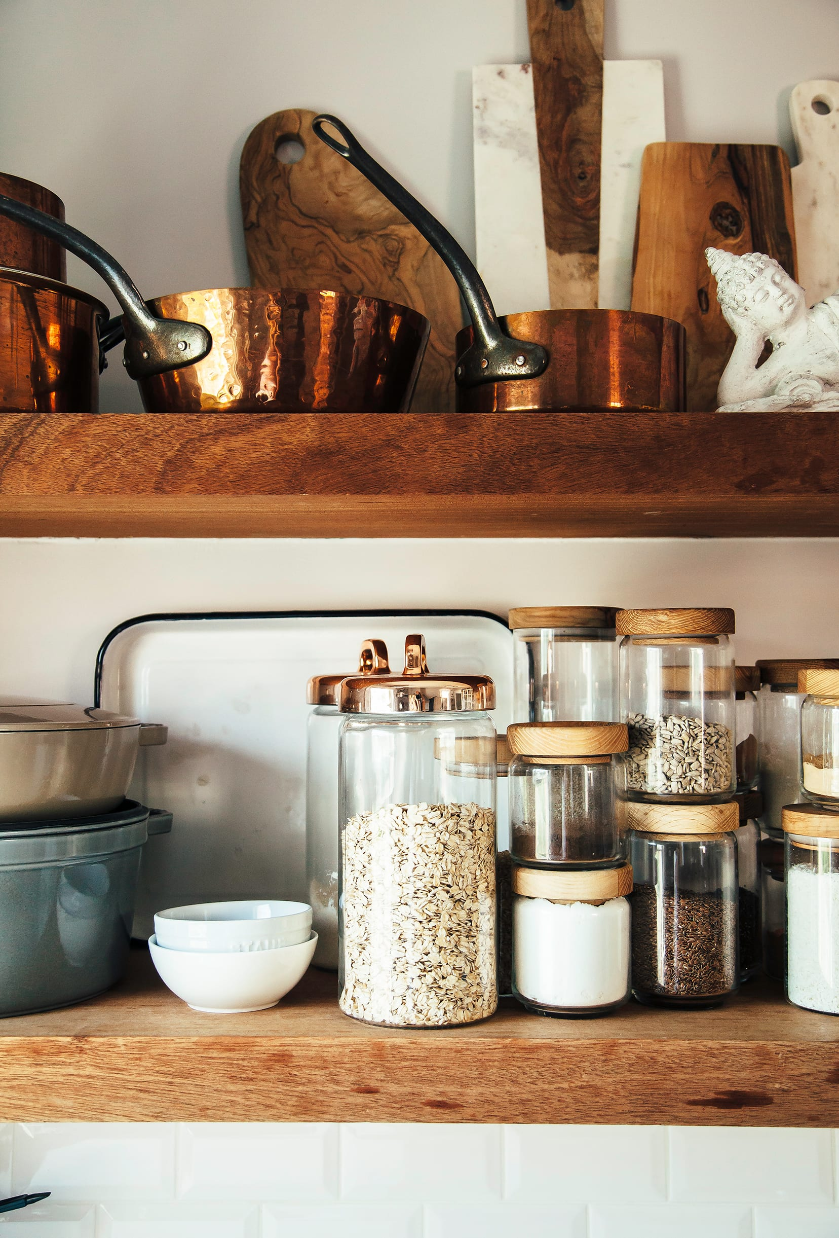 Image shows open kitchen shelves with jars of grains, seeds and spices, as well as copper pots.