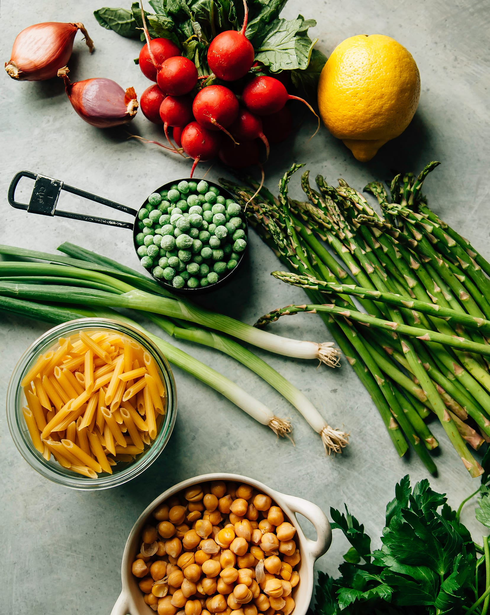 An overhead shot of ingredients for a pasta salad with Spring vegetables over a speckled light blue background.
