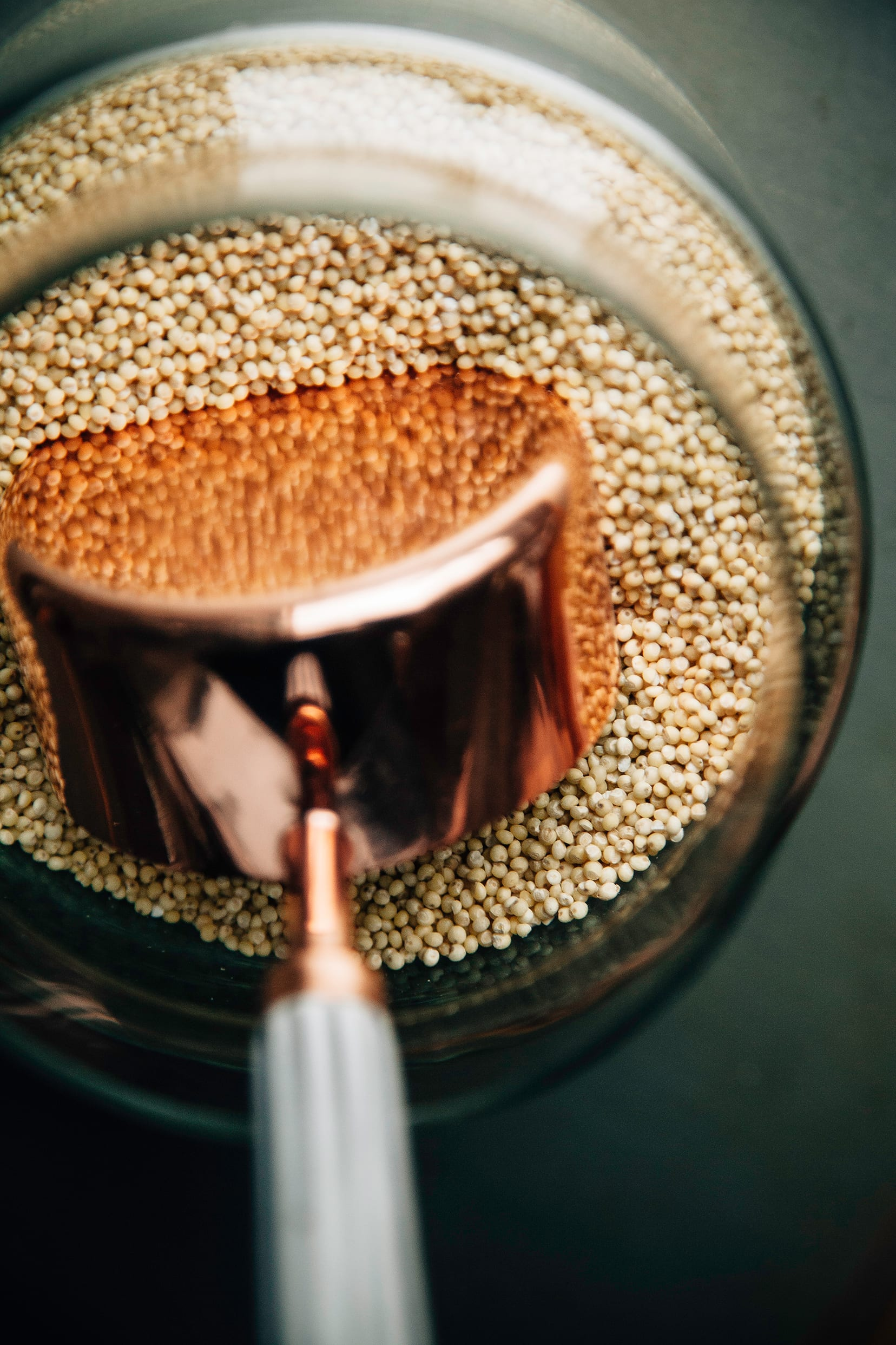 An up close overhead image of a bronze measuring cup inside a jar of dry millet.
