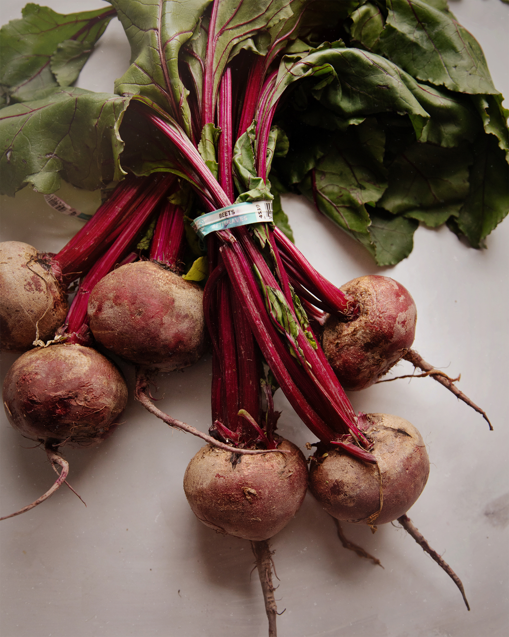 An overhead shot of two bunches of beets with greens on a white background. The lighting is soft and natural.