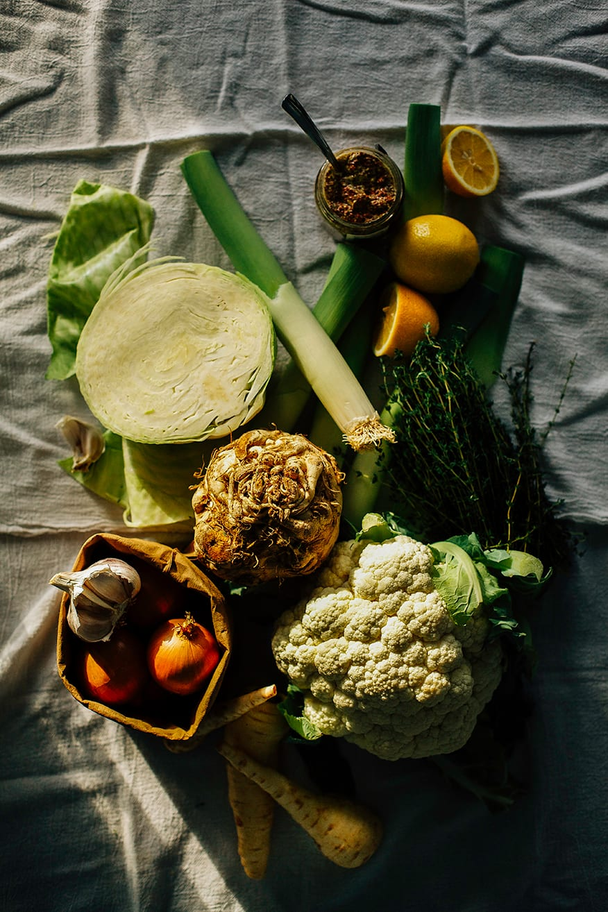 An overhead shot of winter vegetables on a white linen background in harsh light. There is: a halved green cabbage, a head of cauliflower, a bag of onions and garlic, some parsnips, a celery root, lemons, and leeks.