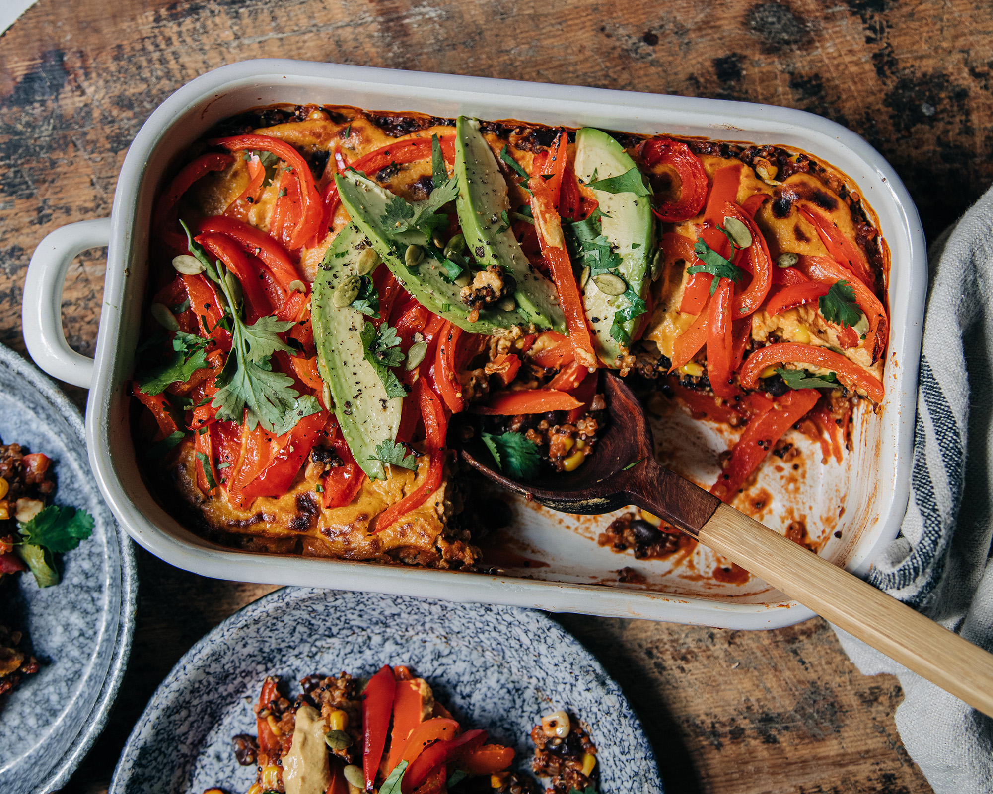 An overhead shot of a vegan casserole topped with sautéed bell peppers, avocado, and chopped cilantro. The casserole dish is white and perched on top of a worn wood surface.