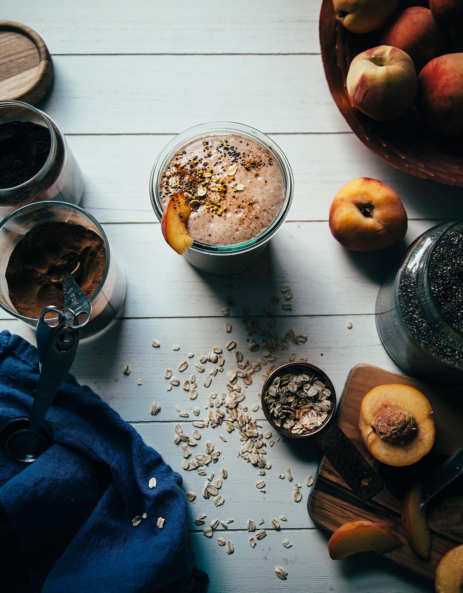 Overhead shot of a peach crumble shake on a white wood background. Ingredients for the shake are scattered nearby, including: sliced peaches, rolled oats, and cinnamon. Included in a roundup of healthy vegan smoothies.