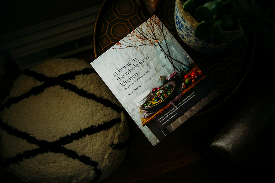 "An overhead shot of ""At Home In The Whole Food Kitchen"" cookbook on a table in dim lighting."