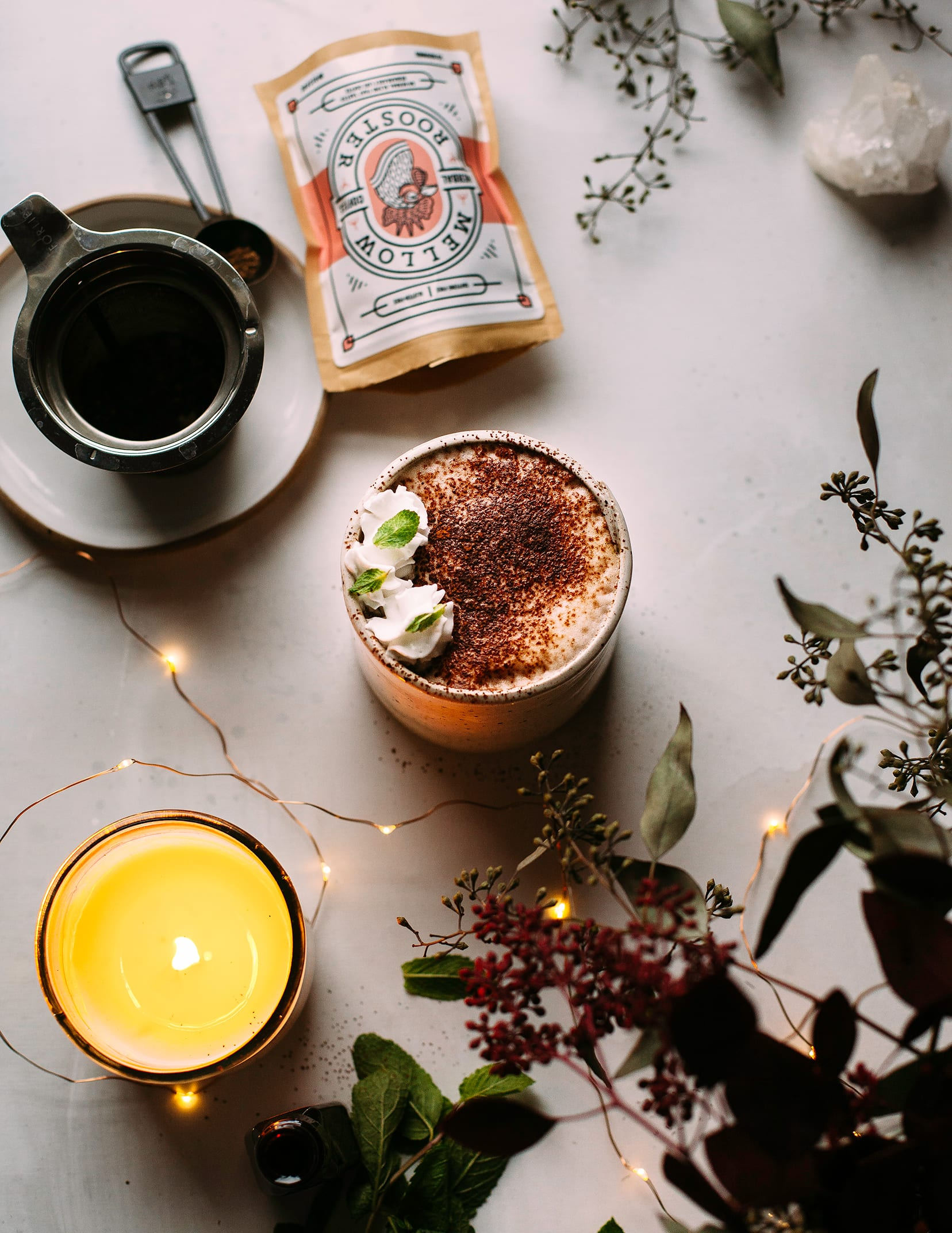 An overhead shot of a frothy drink topped with a dusting of cocoa. Nearby is a string of twinkle lights, some eucalyptus branches, and a bag of herbal coffee.
