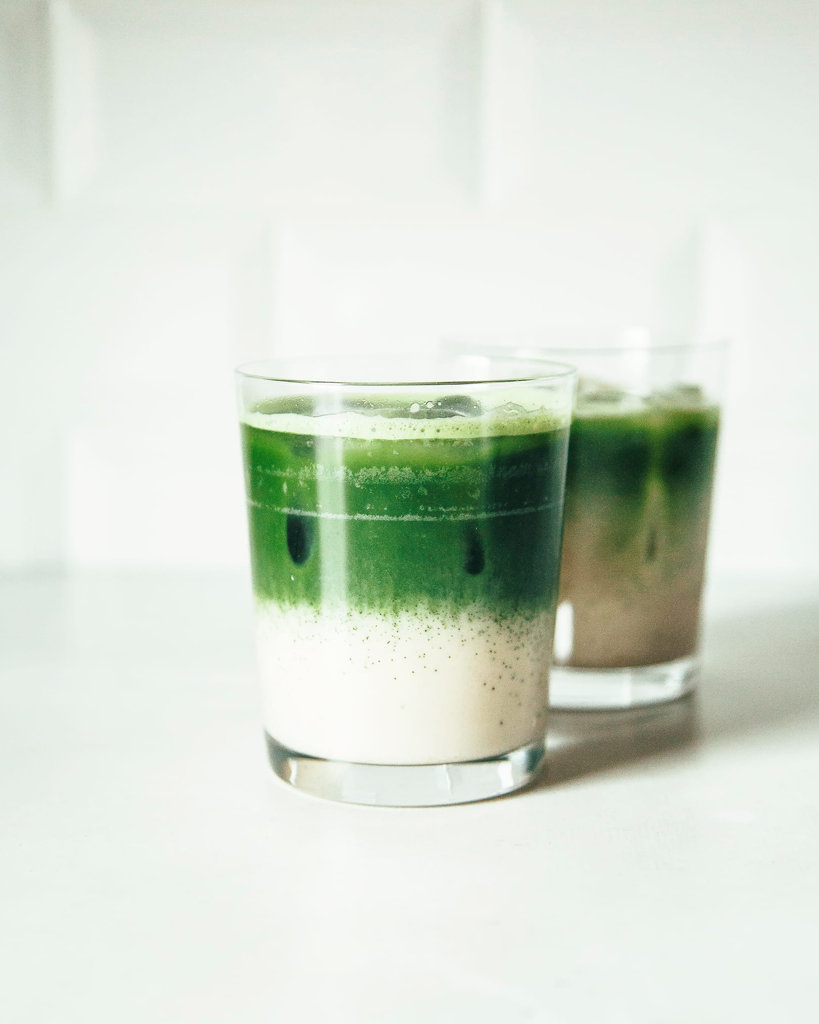 Image shows two glasses with a two-toned beverage against a white background. The bottom half of the beverage is creamy white and the top is bright green.
