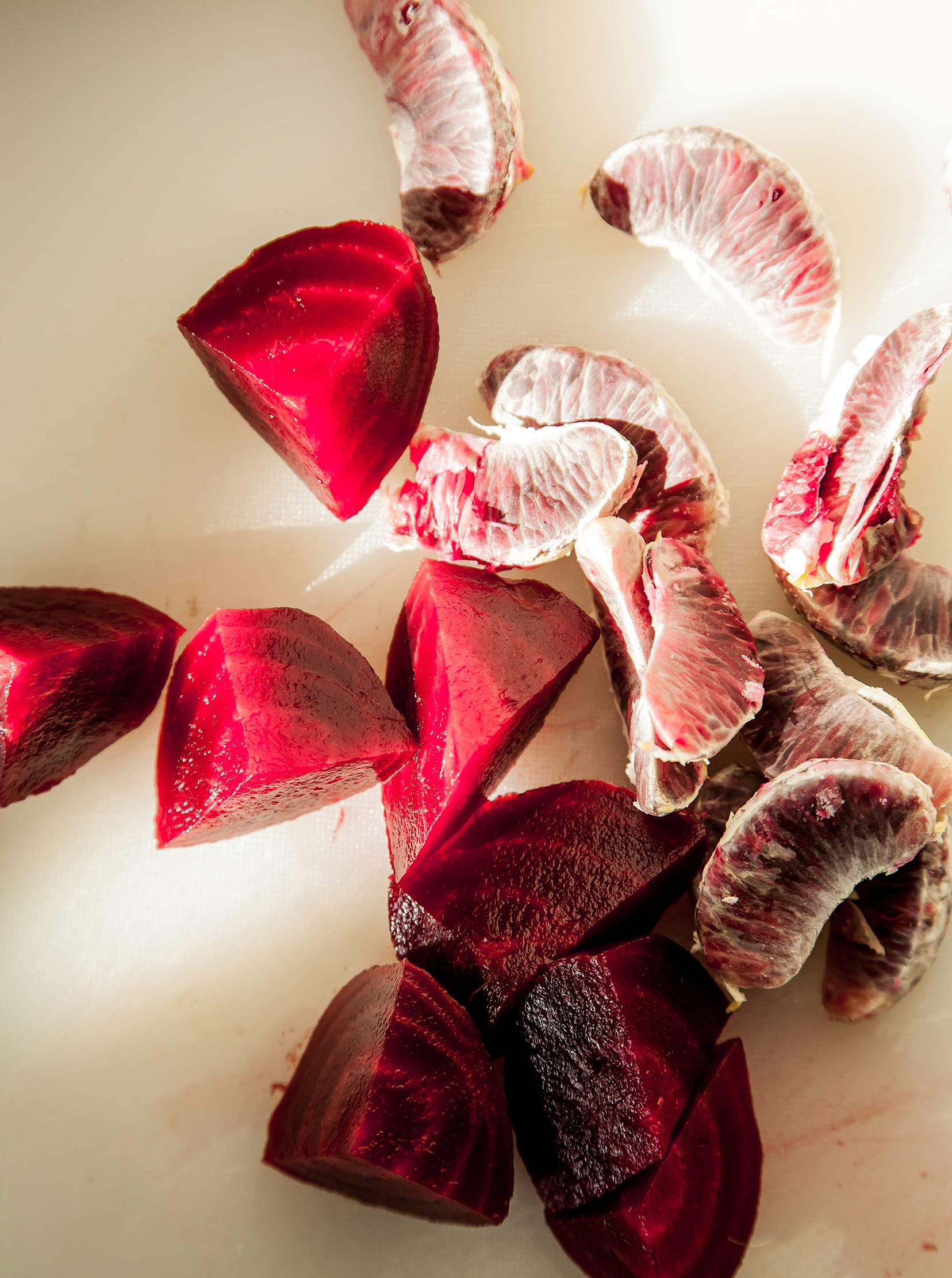 Overhead, up-close shot of a segmented blood orange and diced beet in harsh sunlight on a white background.