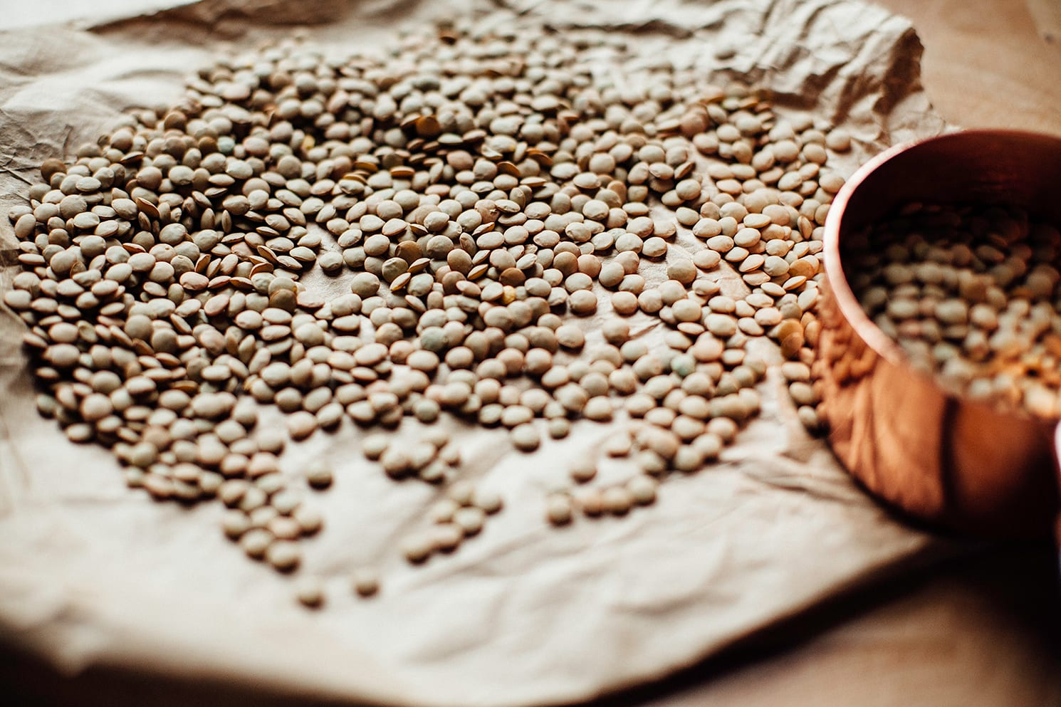 Image shows lentils scattered out on a piece of brown paper.