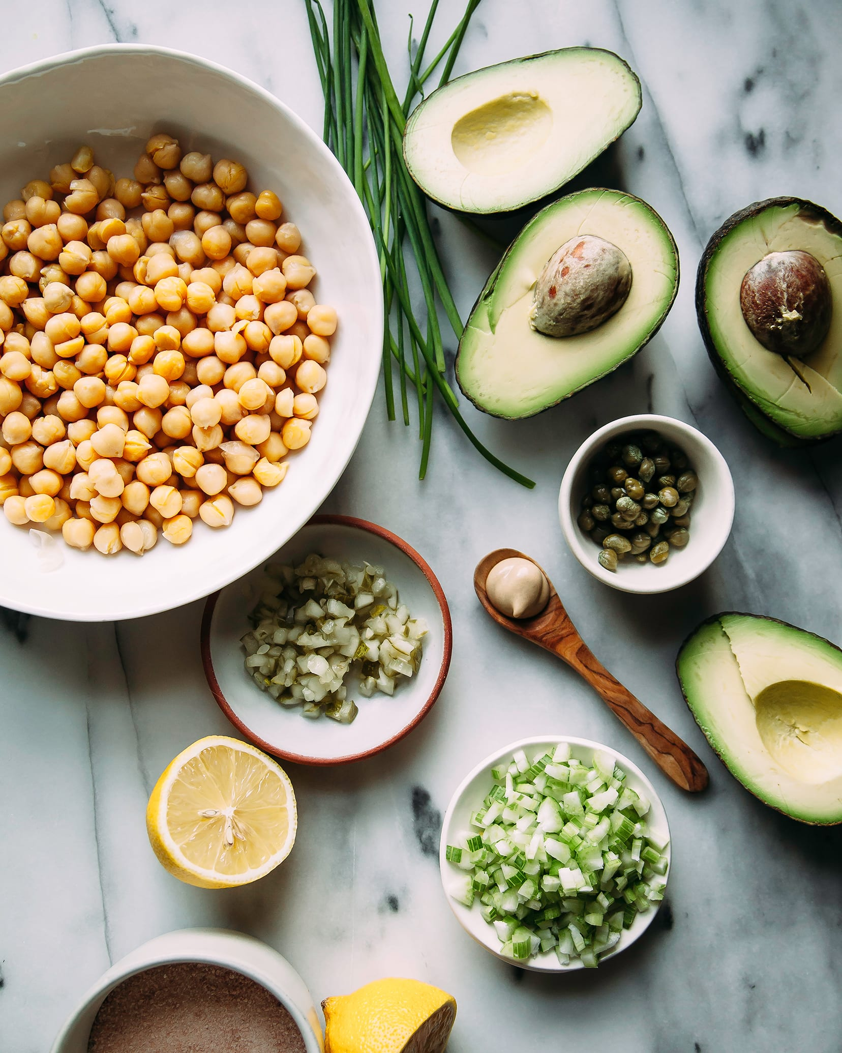 An overhead shot of ingredients for avocado chickpea salad on a grey marble background.