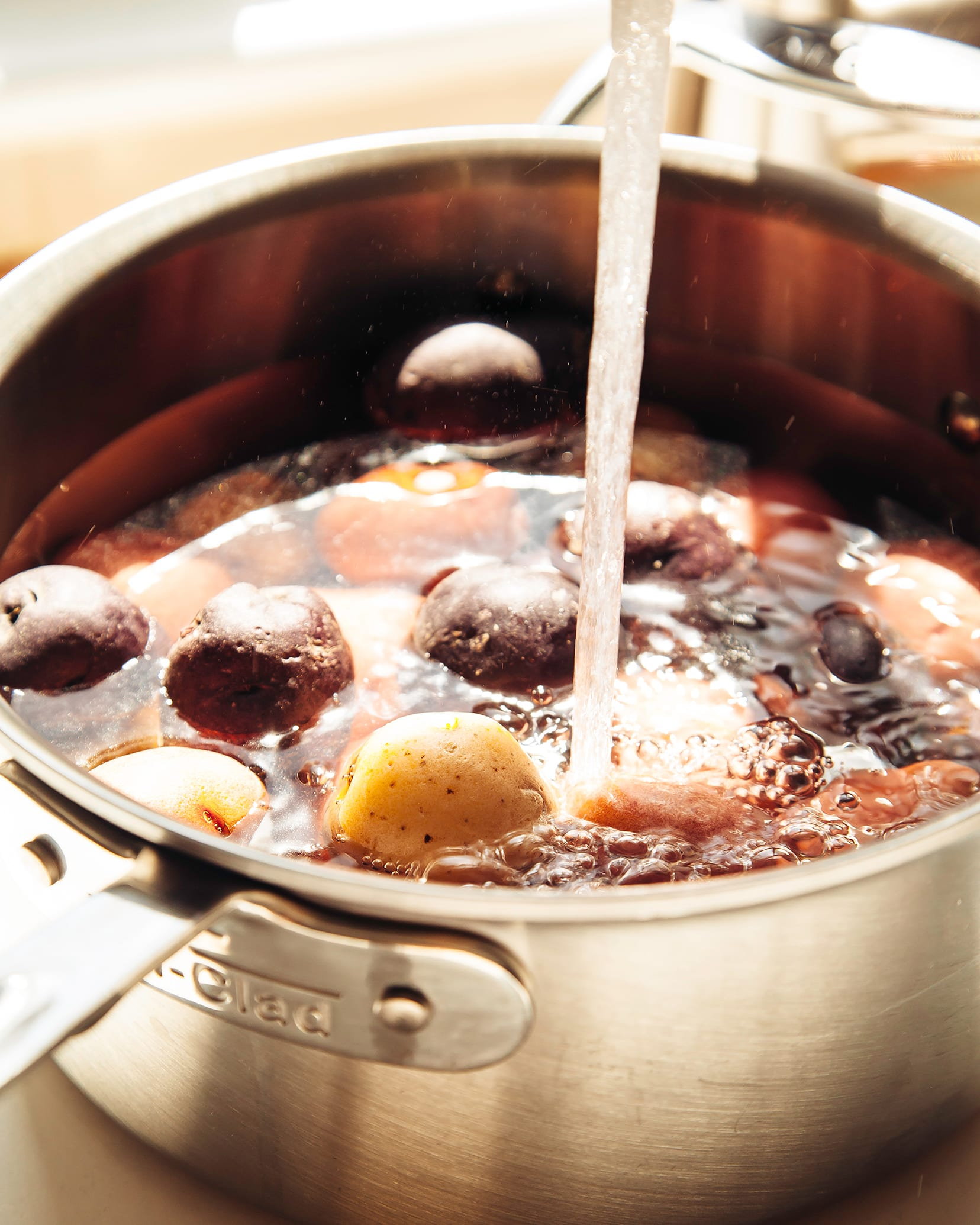 A 3/4 angle shot shows water pouring into a saucepan of baby potatoes in bright, direct sunlight.