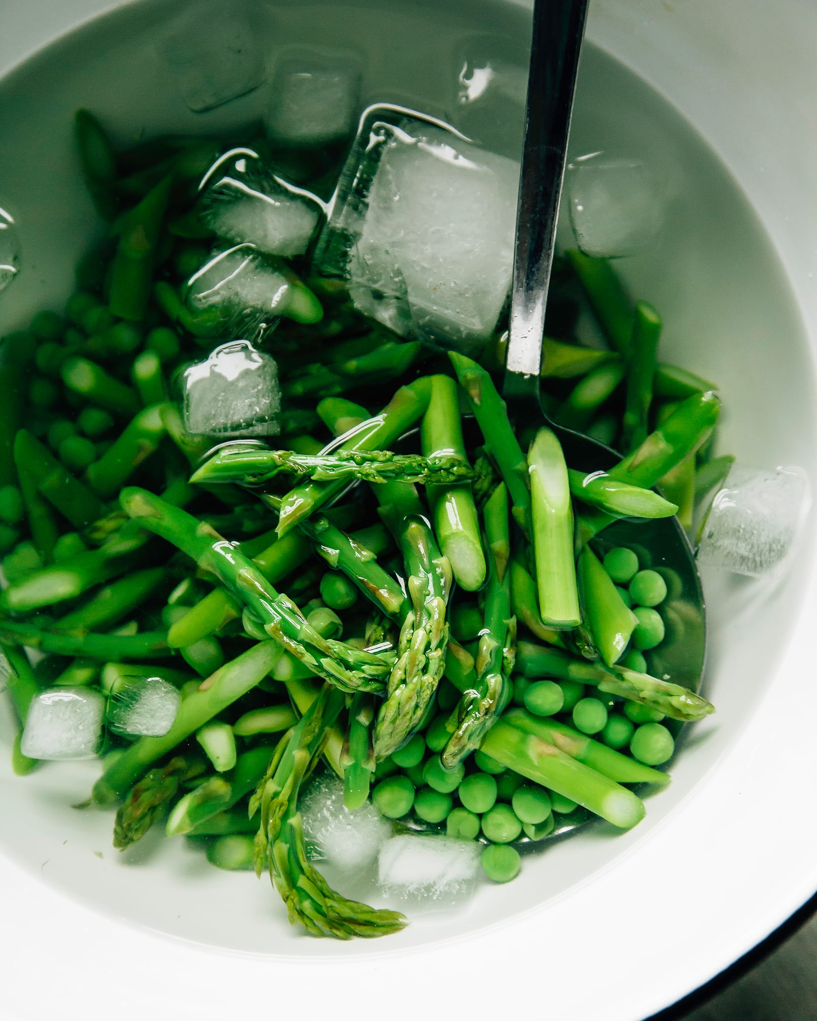 An overhead shot of green vegetables in an ice water bath in a white bowl.