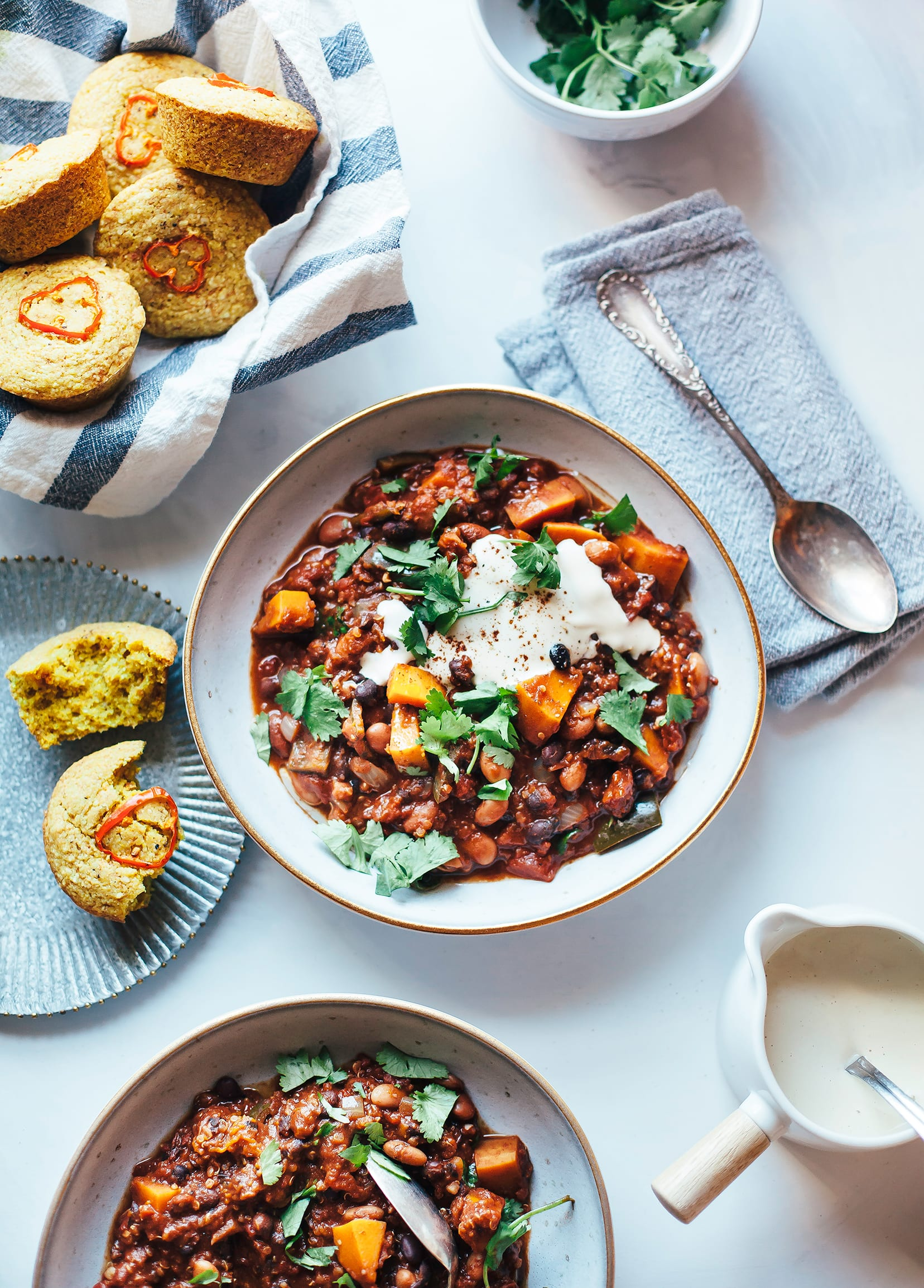 An overhead shot of SMOKY SQUASH CHILI WITH QUINOA, PINTO & BLACK BEANS with cornbread muffins on the side.