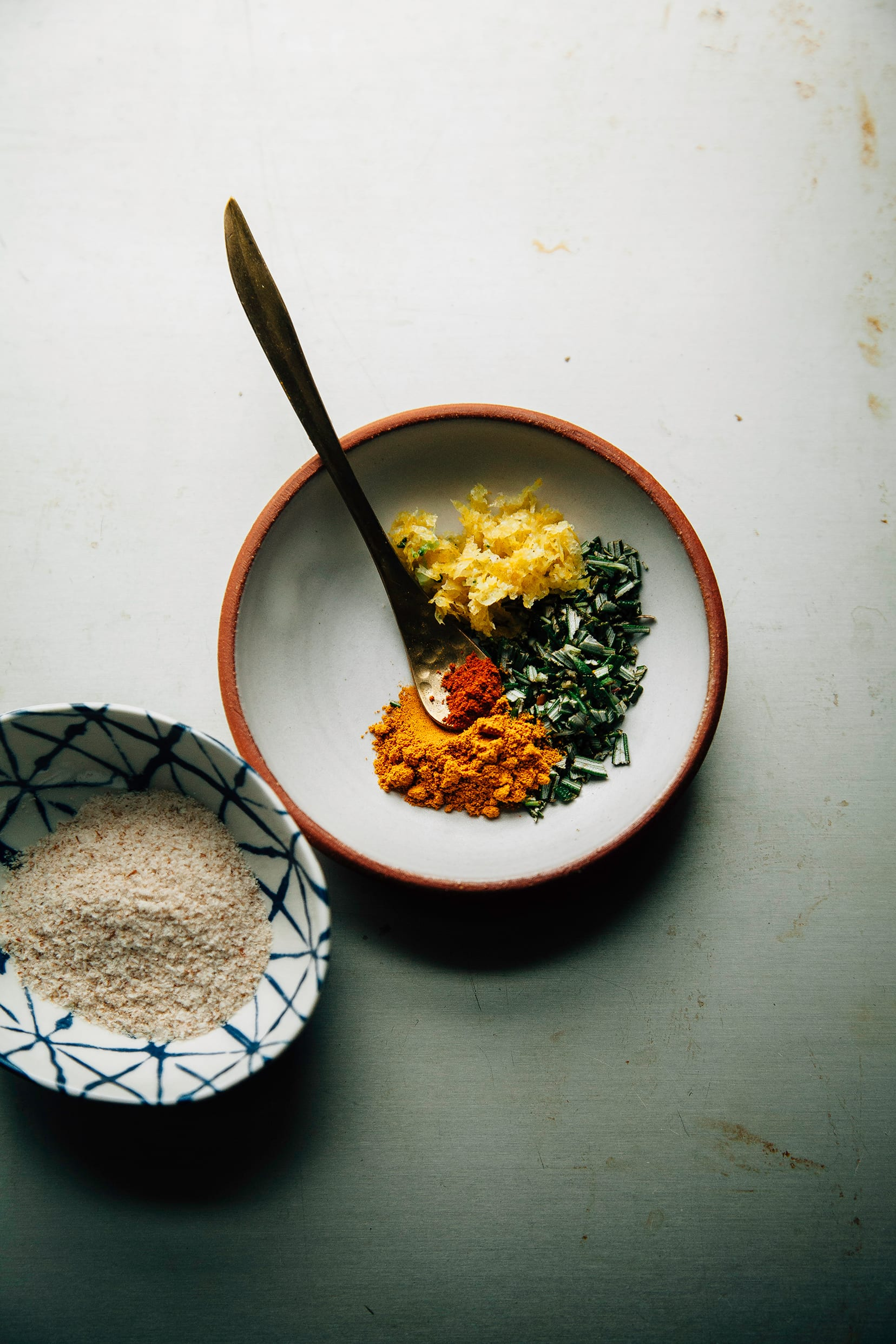 An overhead shot of a small bowl with chopped herbs and spices.