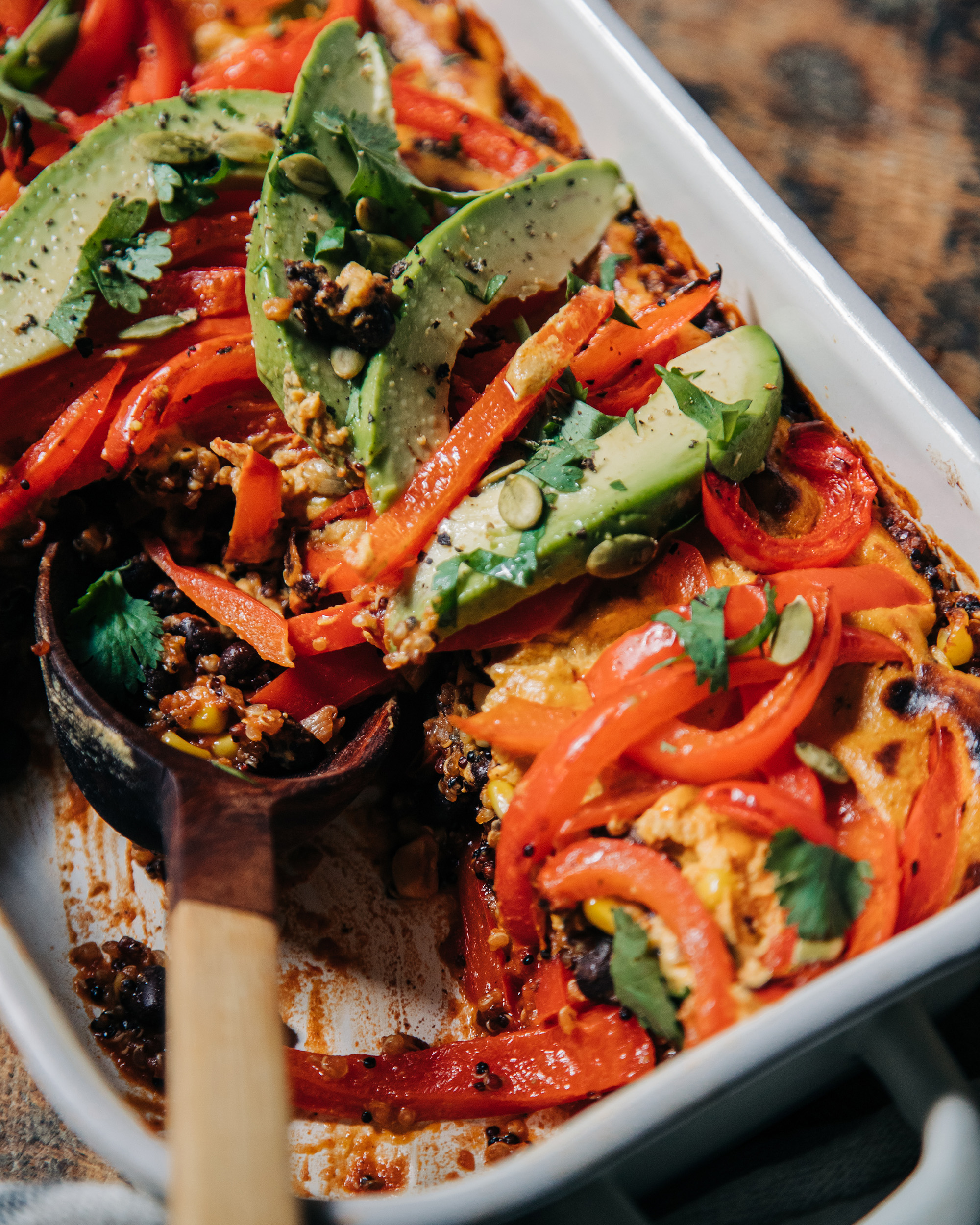 A 3/4 shot of a vegan casserole topped with sautéed bell peppers, avocado, and chopped cilantro. The casserole dish is white and perched on top of a worn wood surface.