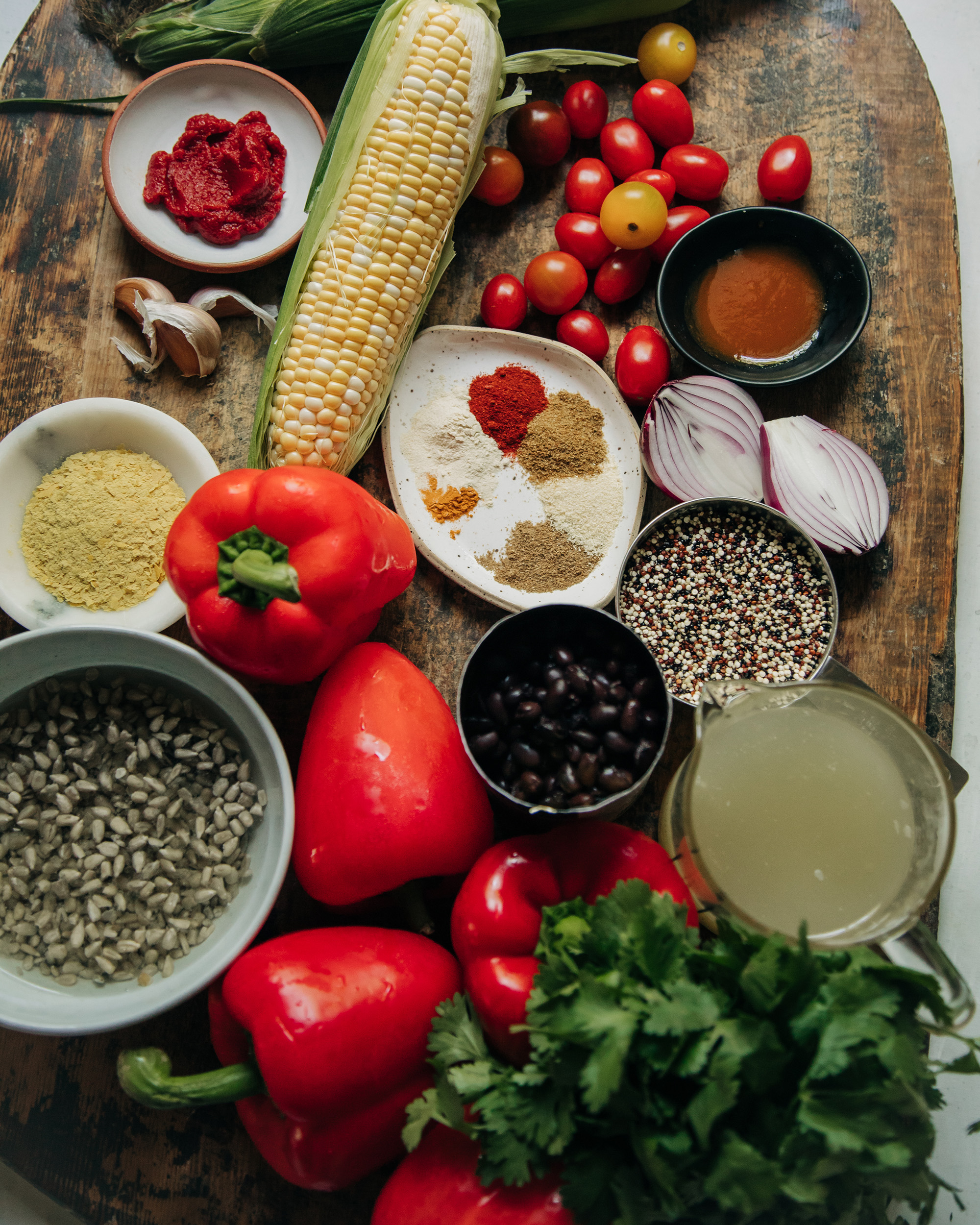 An overhead image of ingredients for a hearty vegan meal, including corn on the cob, a can of black beans, various spices, red bell peppers, cilantro, cherry tomatoes, garlic, and quinoa.