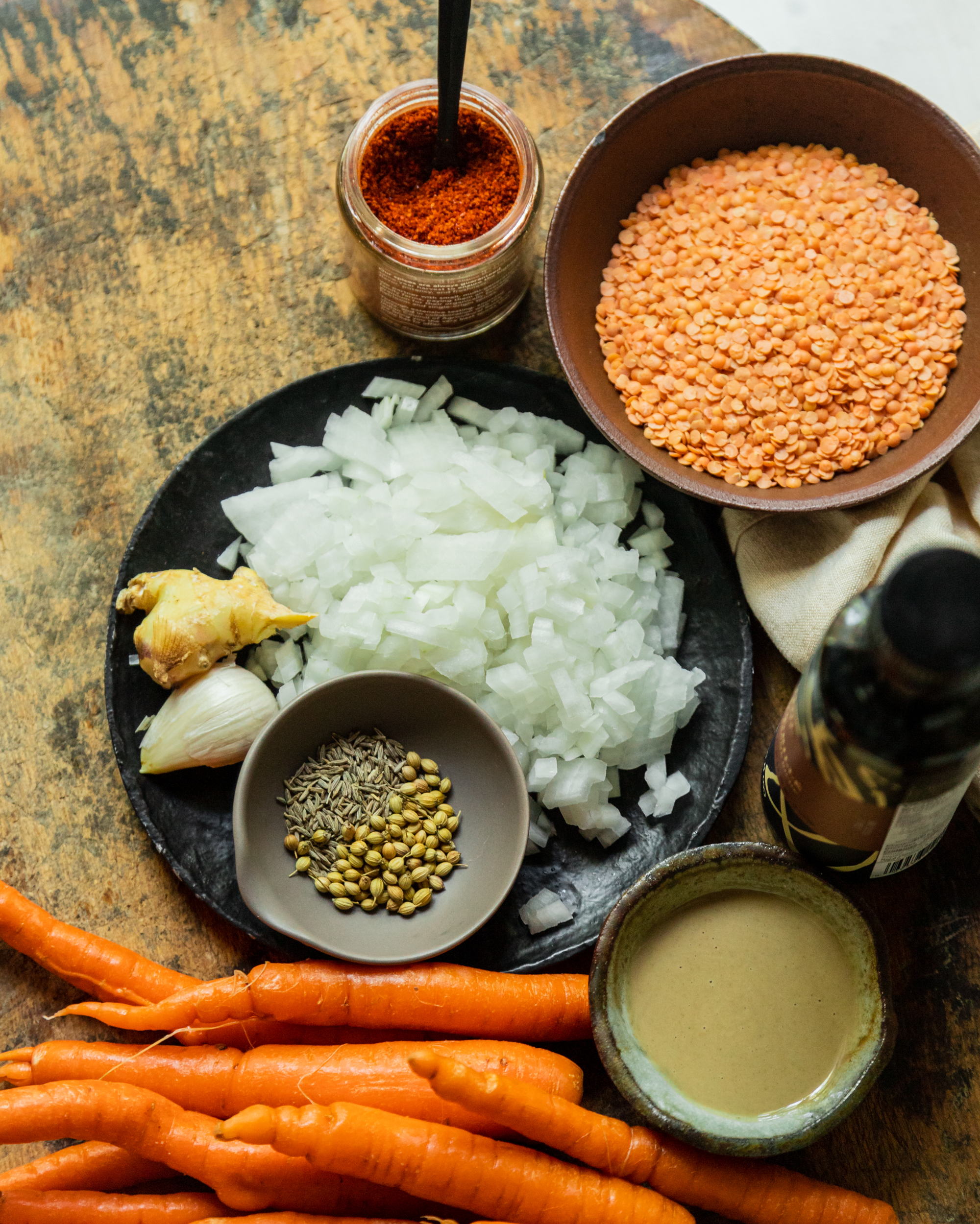 An overhead shot of ingredients for a spicy sesame carrot soup on a wood background.