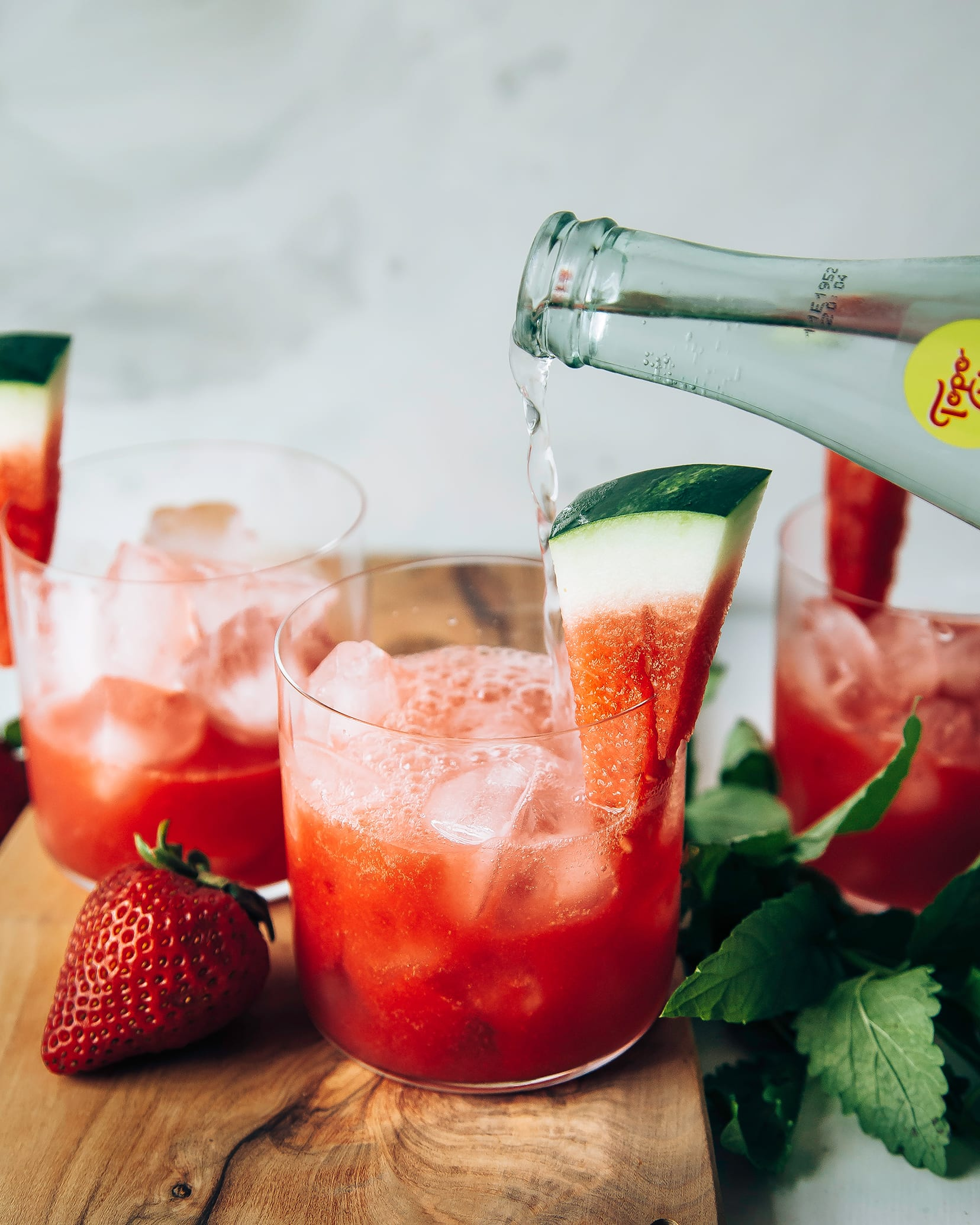 Photo displays sparkling strawberry watermelon limemade being topped with sparkling water.