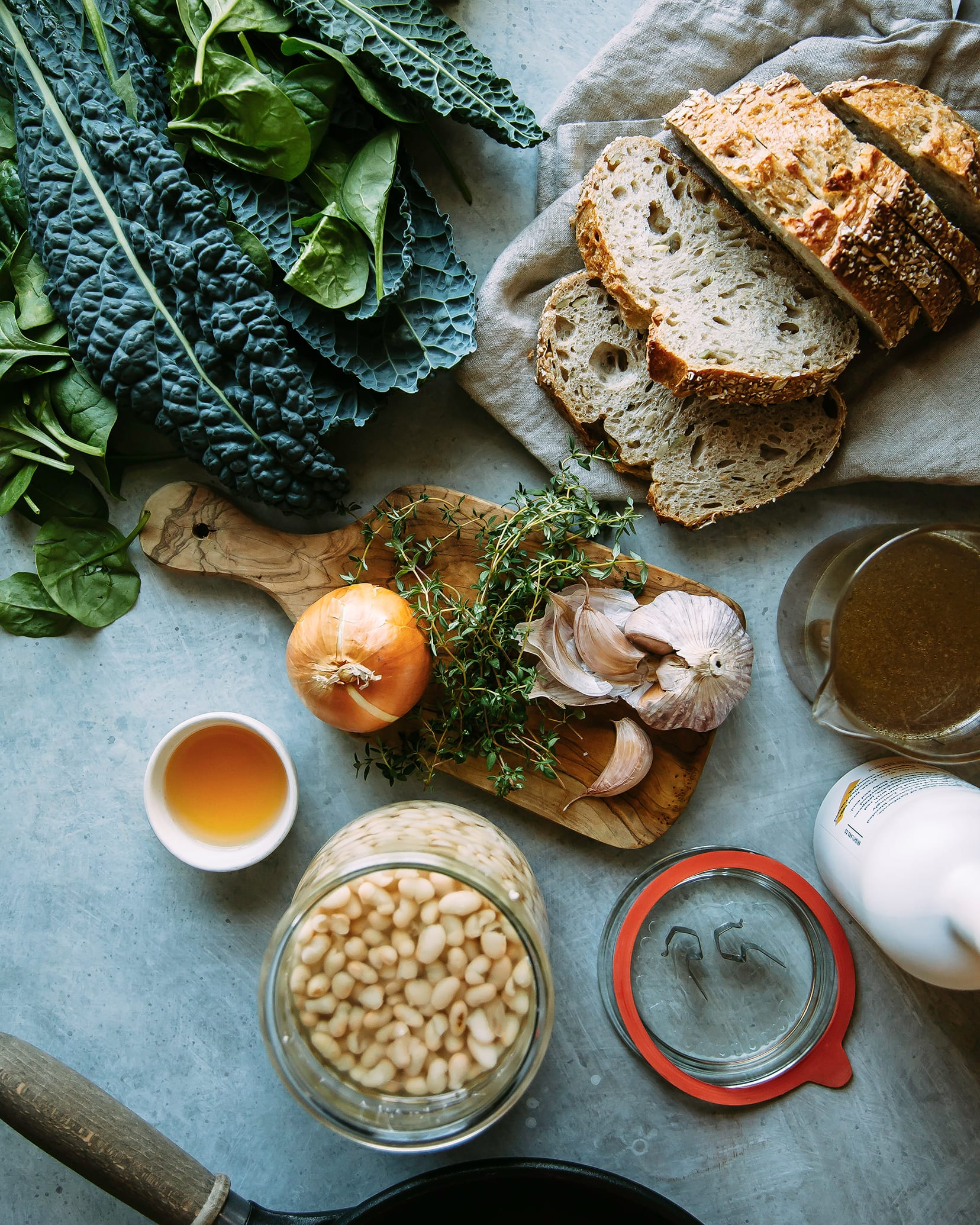An overhead shot of ingredients for creamy white beans with greens plus some sliced bread.