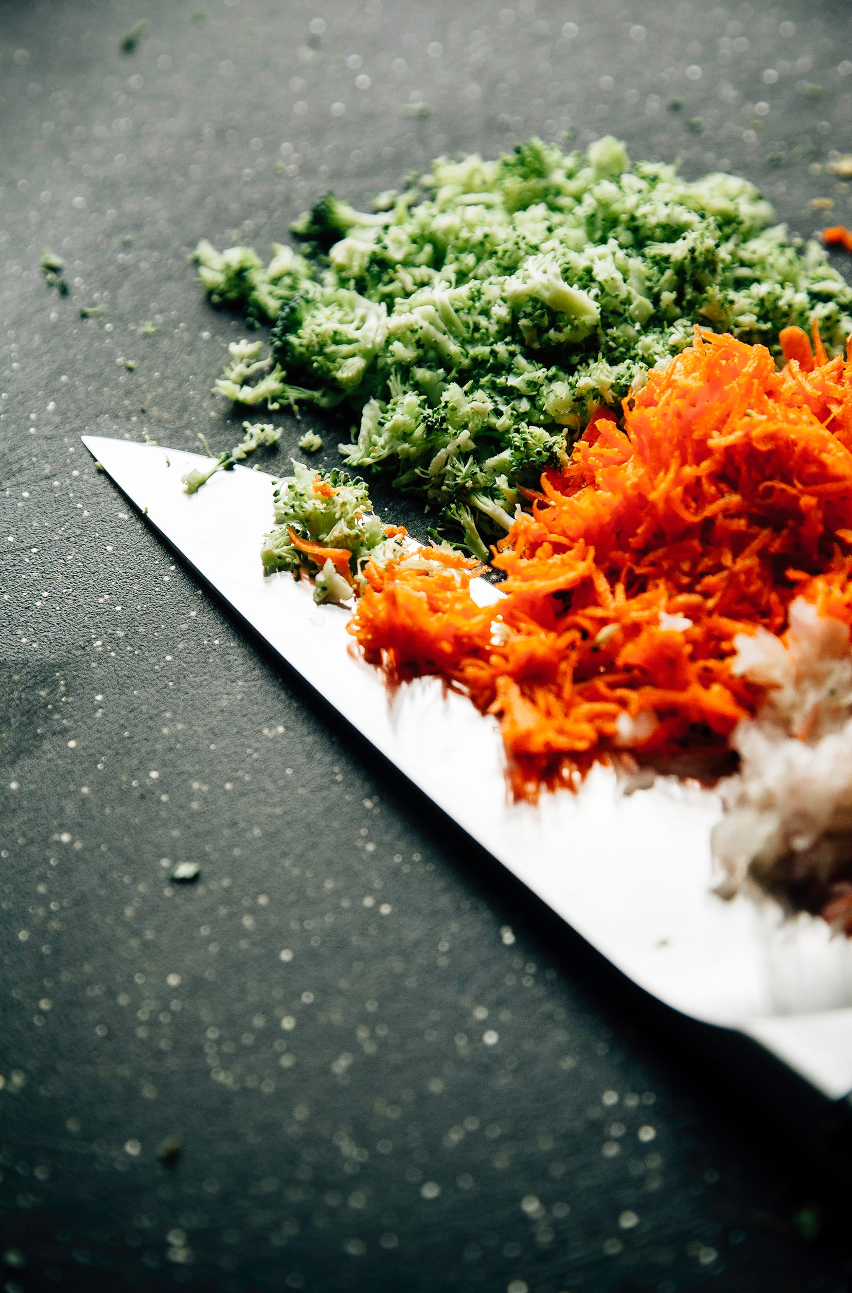 A 3/4 angle image of finely chopped carrots and broccoli.