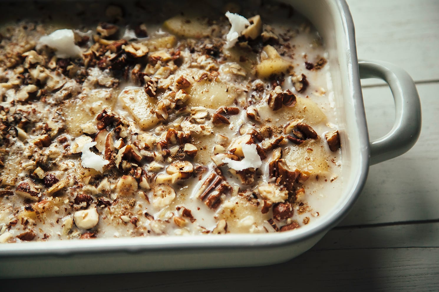 Image shows an assembled apple spice baked oatmeal in a white enamelware baking dish, pre-bake.
