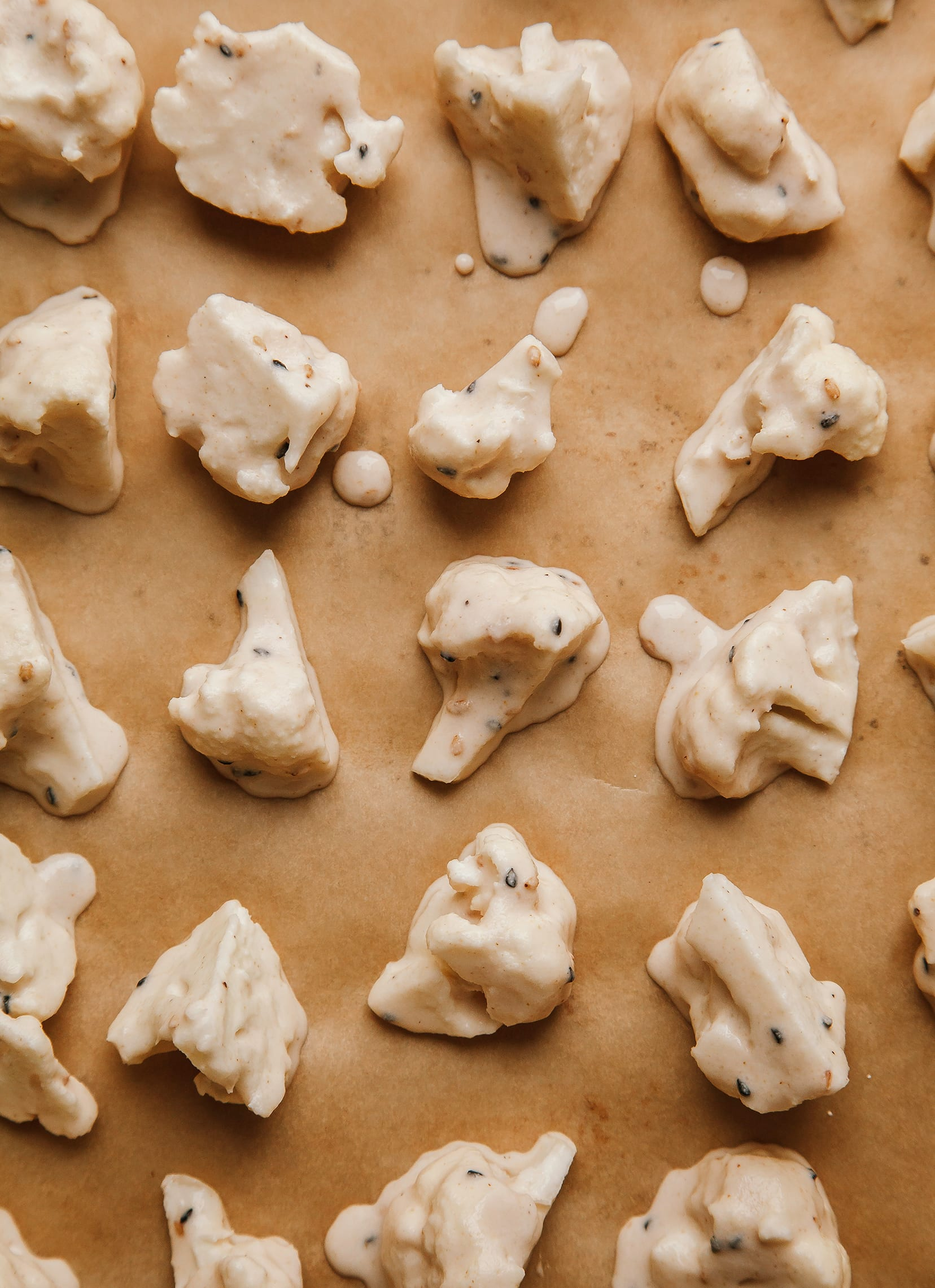 Image shows cauliflower florets coated in batter on a parchment-lined baking sheet.