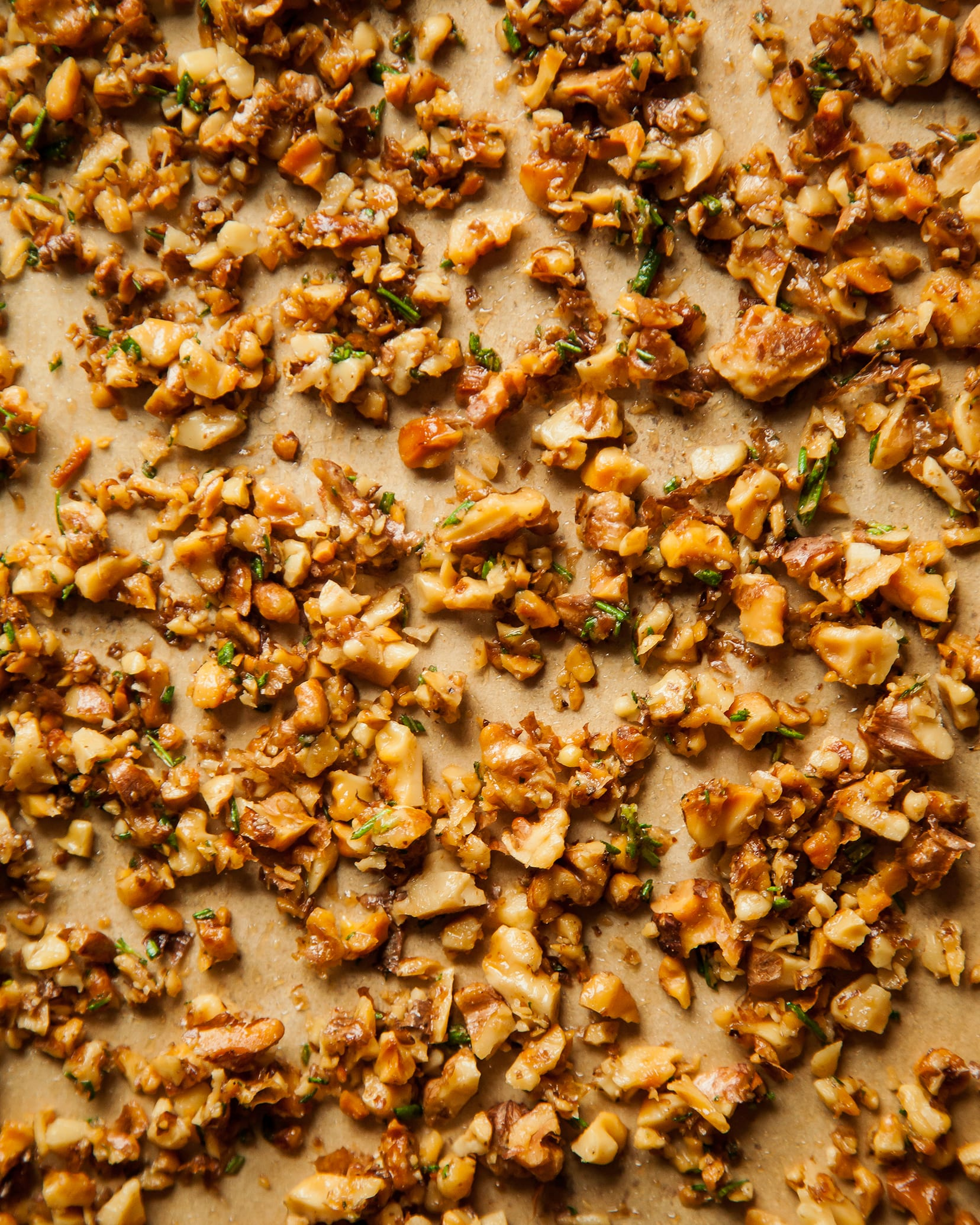 An overhead of chopped and toasted walnuts on top of parchment paper.