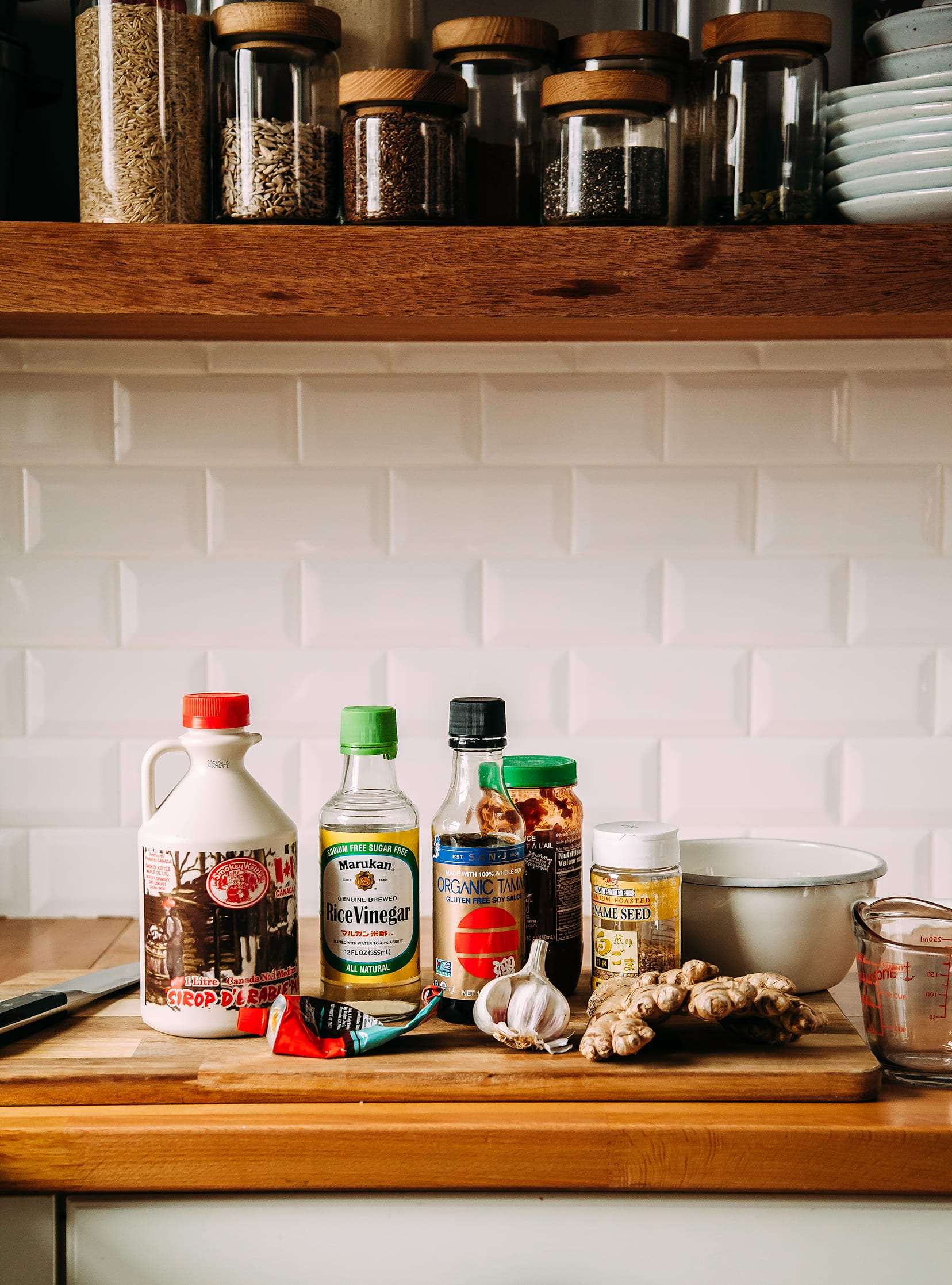 A kitchen counter scene with ingredients for a sesame, ginger, chili sauce.
