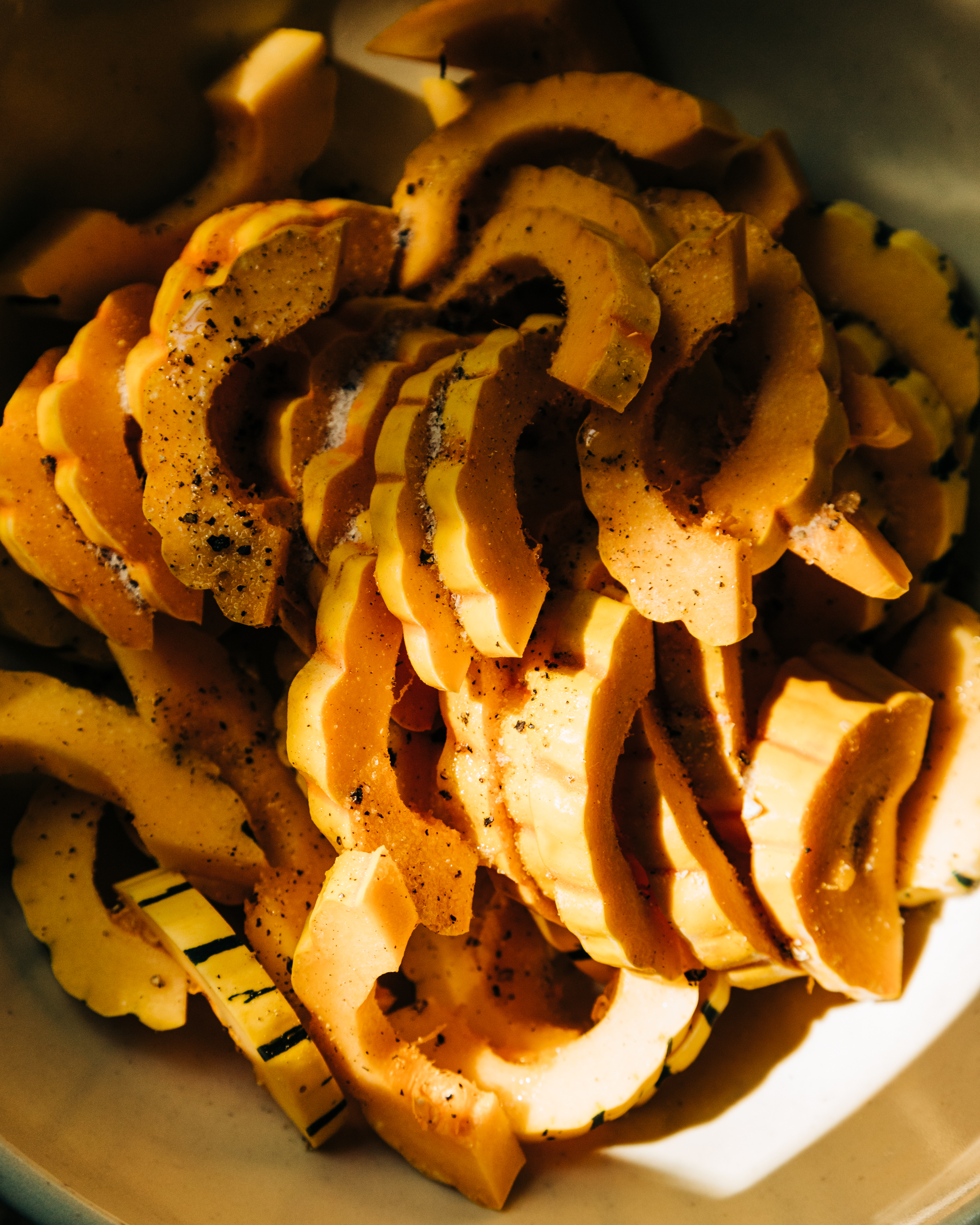 An up close, overhead shot of sliced delicata squash in harsh sunlight.