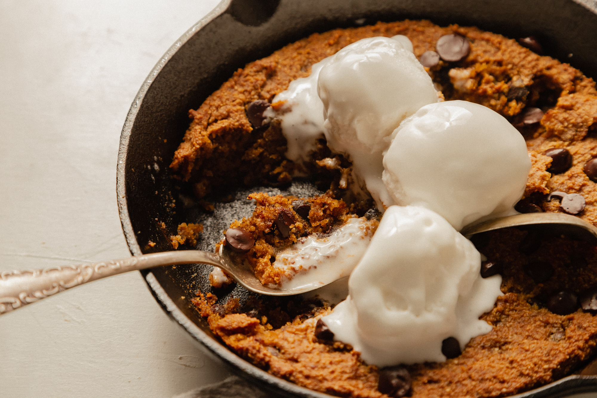 A 3/4 angle shot of a slightly orange pumpkin chocolate chip skillet cookie topped with 3 scoops of vanilla ice cream. The ice cream is melt-y and several bites have been taken out of the cookie.