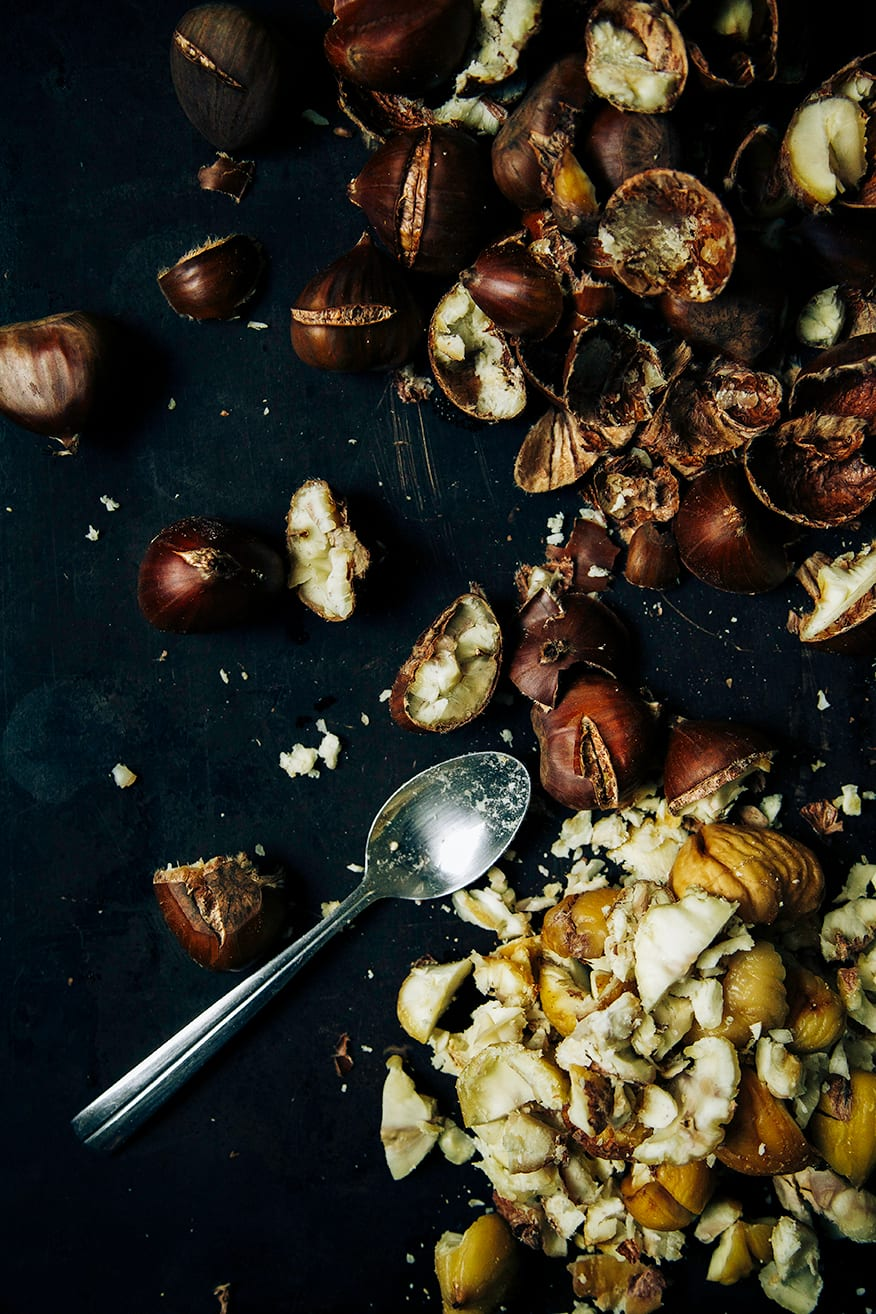 An overhead shot of roasted and peeled chestnuts on a black metal sheet pan.