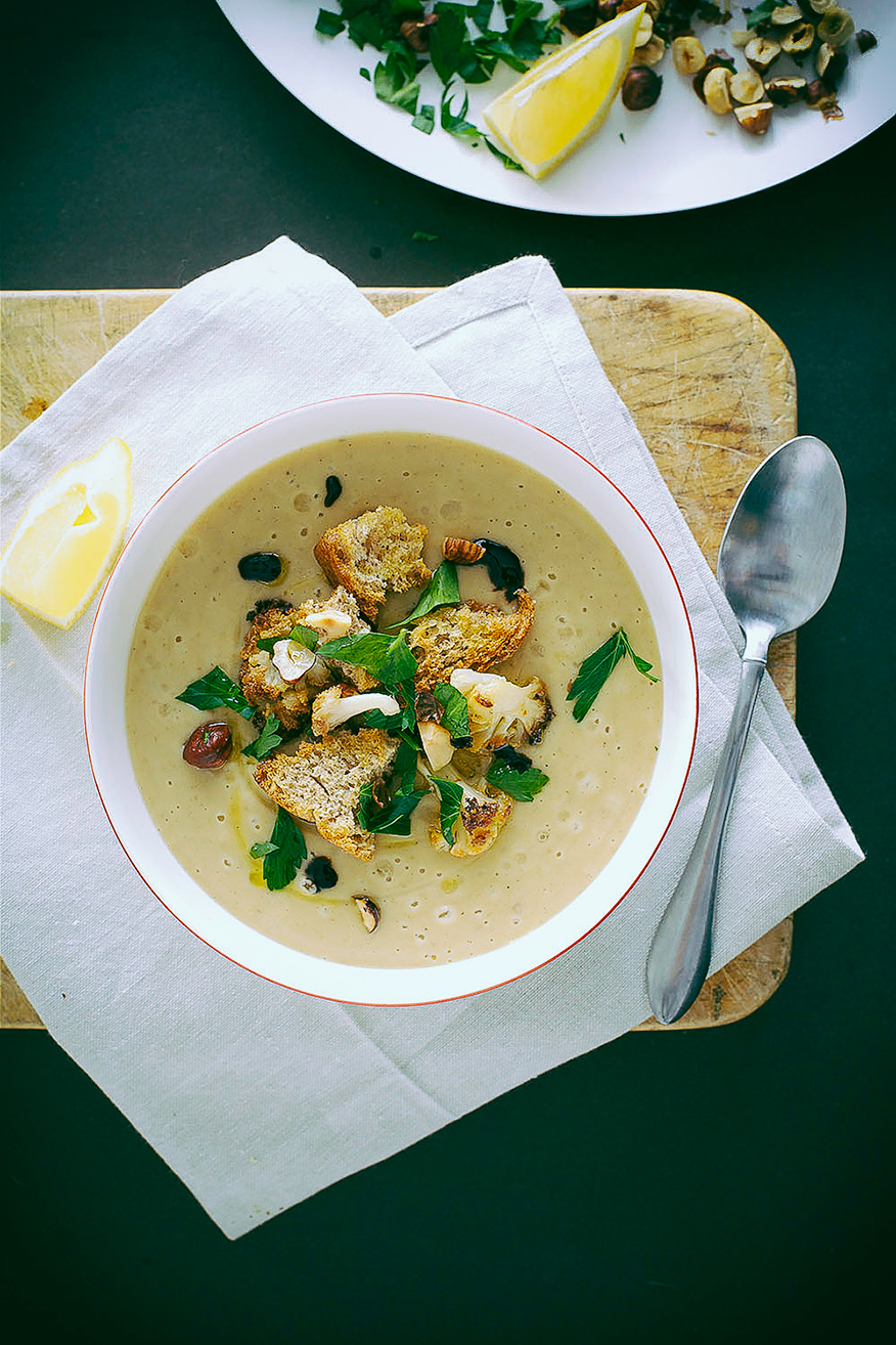 An overhead shot of a bowl of vegan roasted cauliflower soup, garnished with croutons and chopped parsley. The soup is beige. The bowl is on a beige napkin, which is on top of a wooden cutting board.