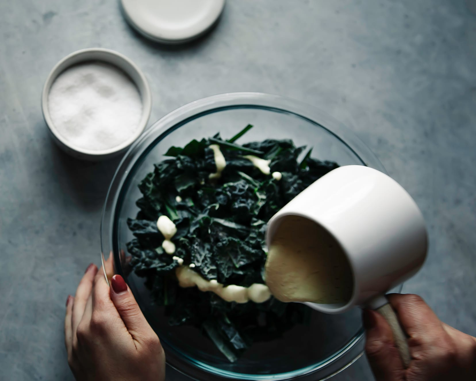 Image shows a hand pouring a creamy dressing over some chopped kale in a bowl.