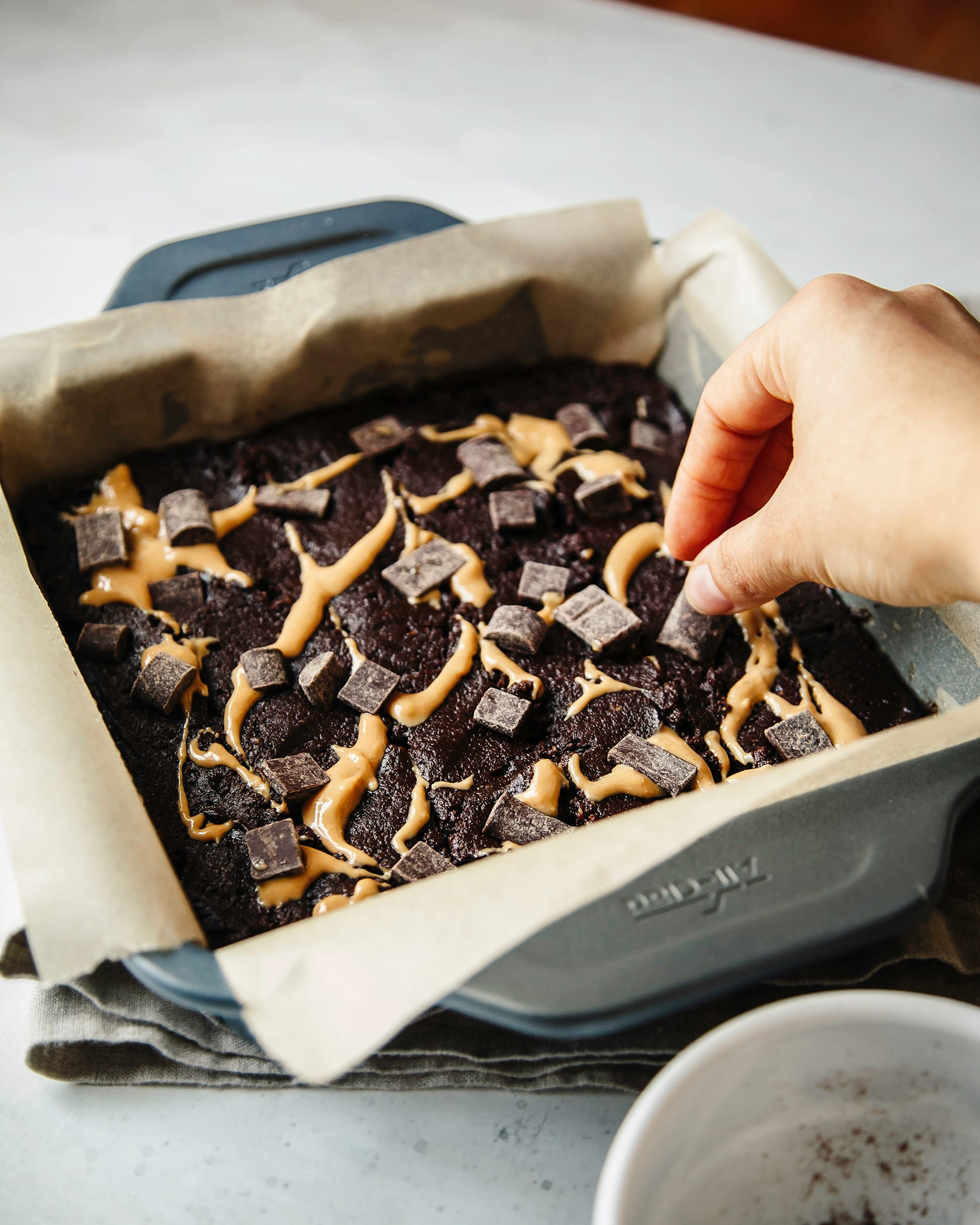 A 3/4 angle shot of a hand placing chocolate chunks on top of a pan of brownies, about to be baked.