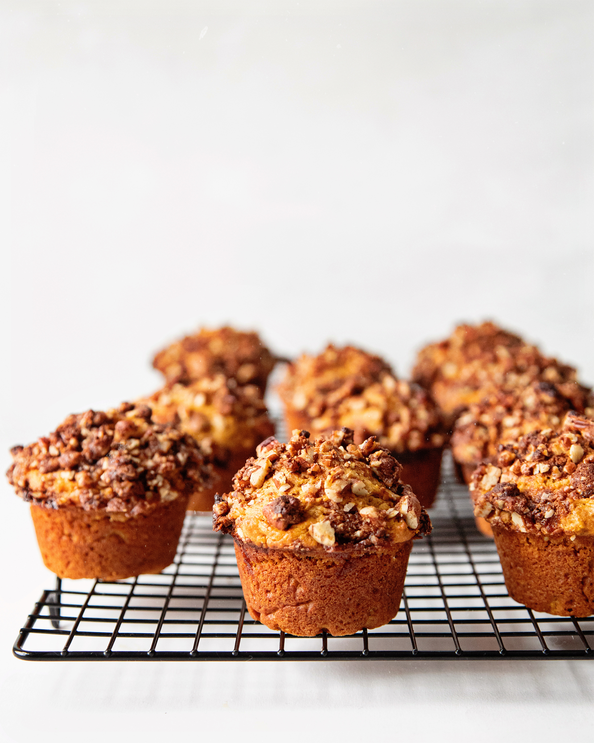 A head on shot of vegan sweet potato muffins with pecan streusel, sitting on top of a black cooling rack with a white background.