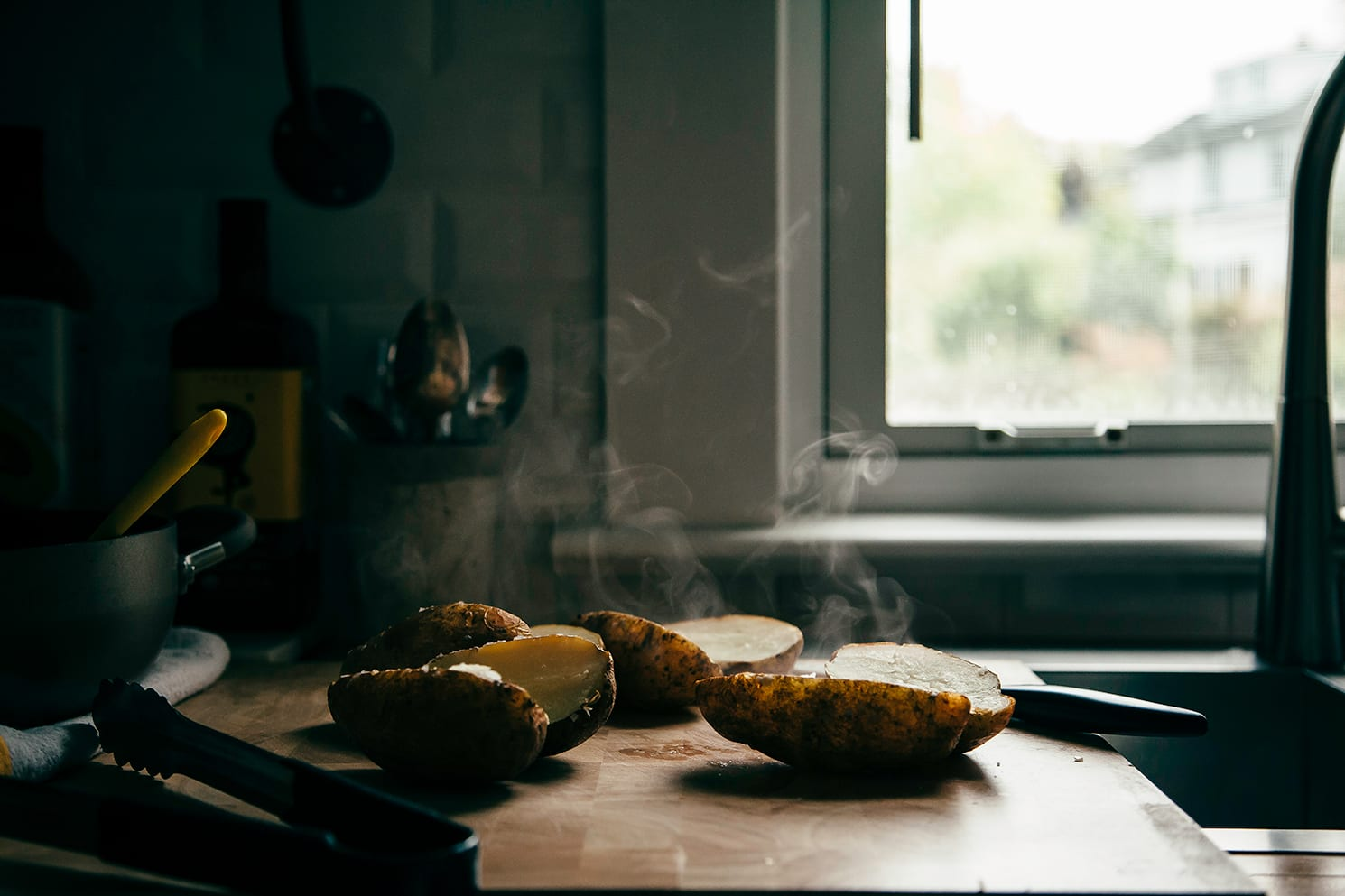 Image shows steaming, split open baked potatoes on a cutting board.