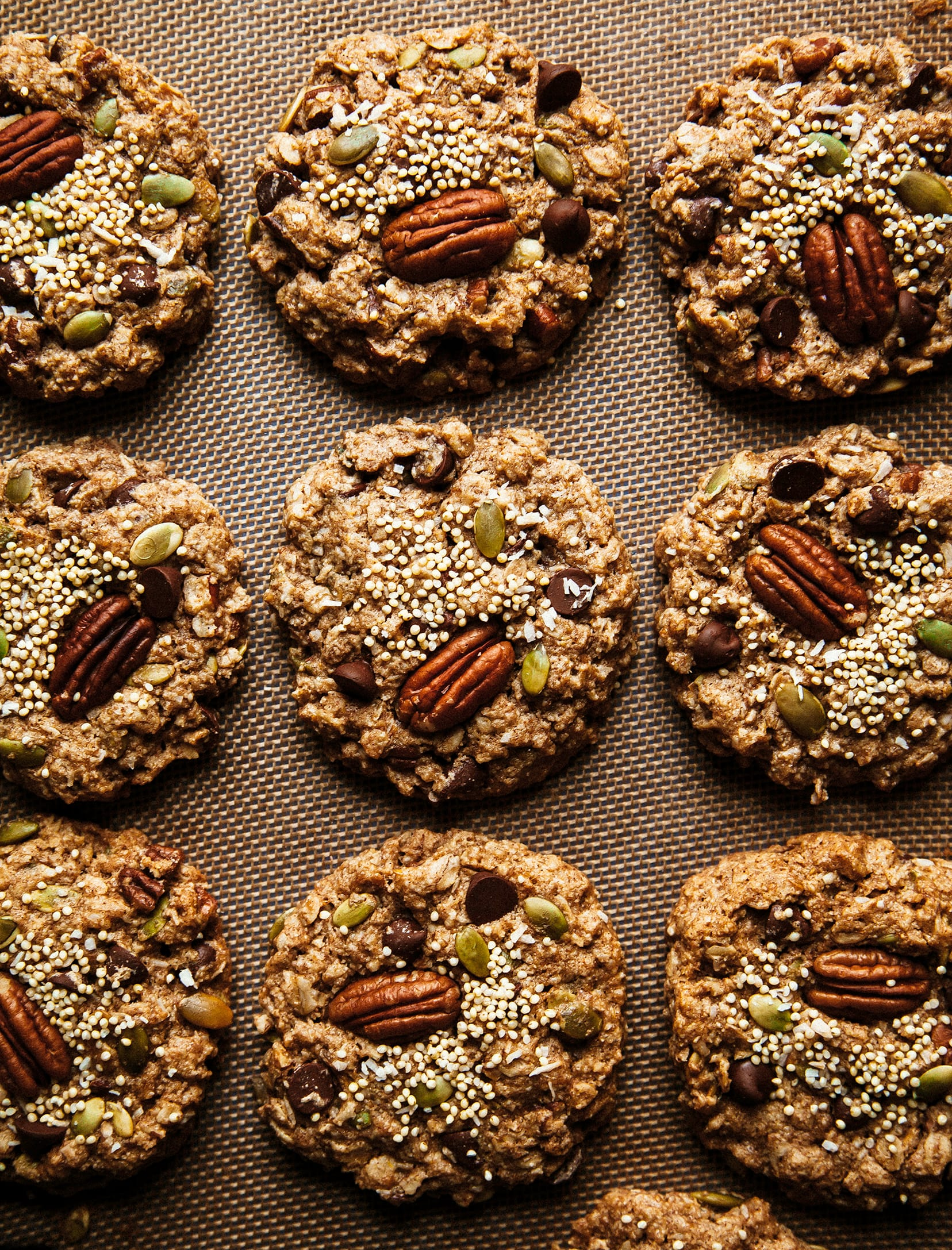 Nutty vegan breakfast cookies shot from overhead. A grid of 9 cookies studded with pecans, millet and pumpkin seeds.