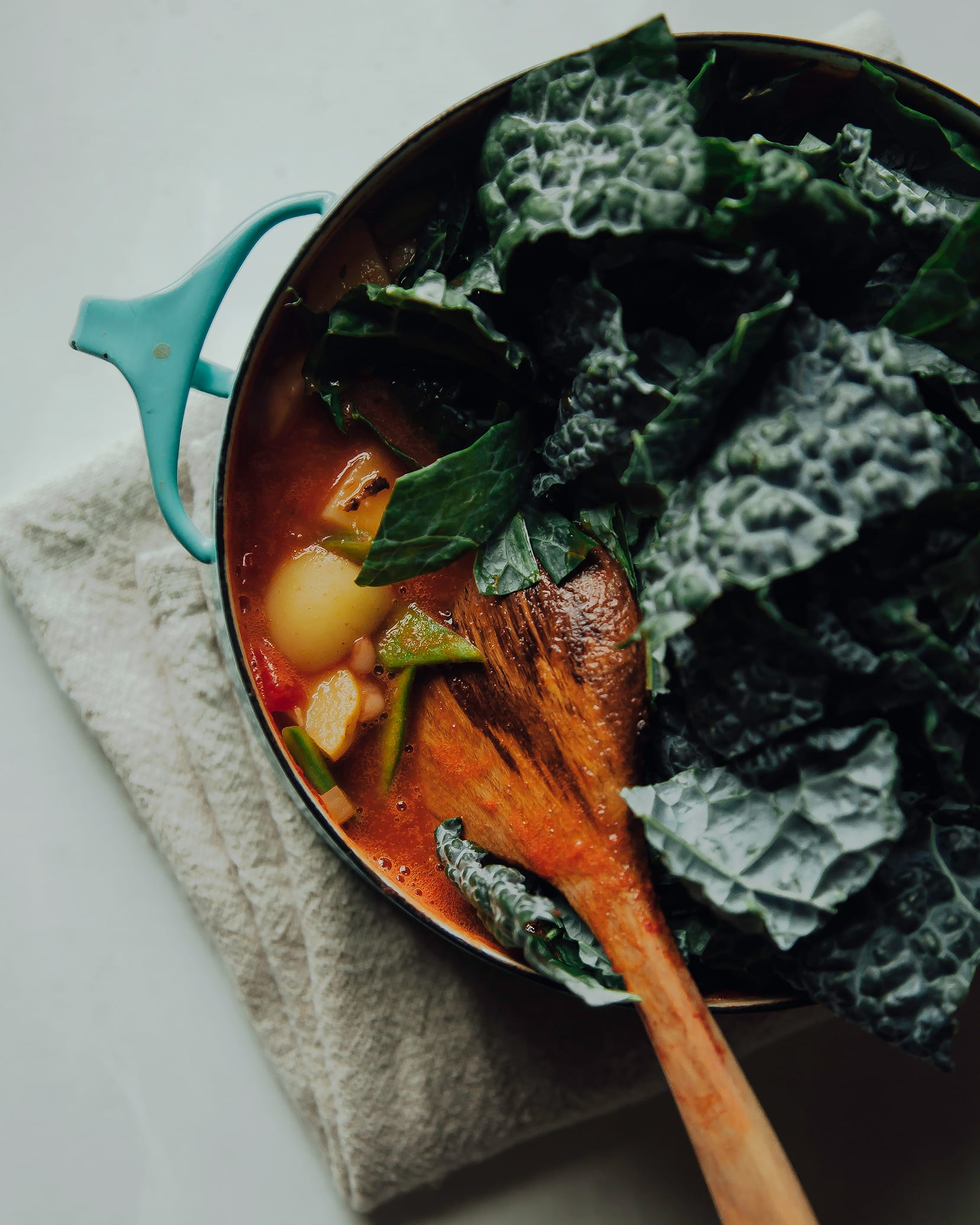 Image shows chopped kale being added to a pot of stew.