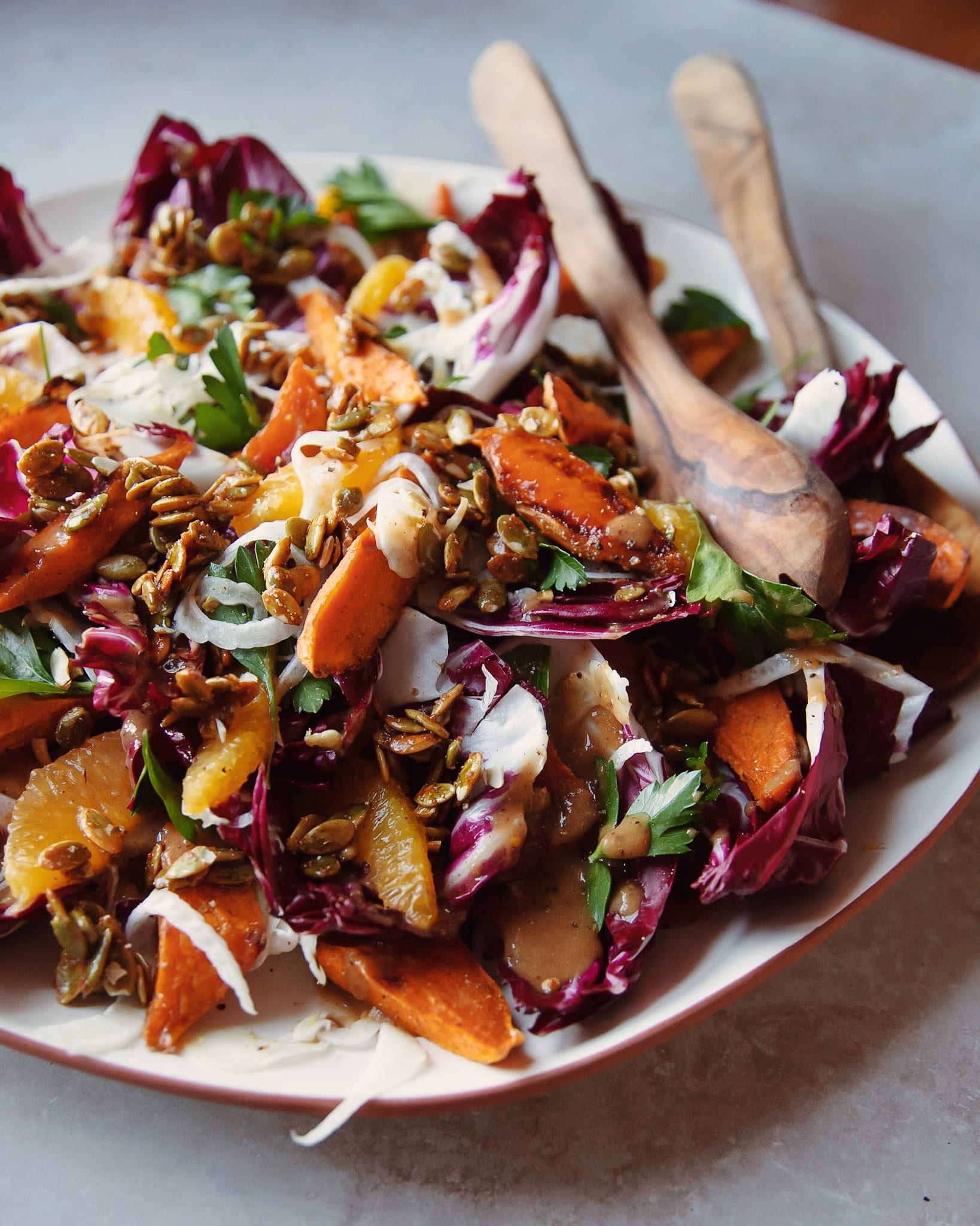 a 3/4 shot of a roasted sweet potato and radicchio salad with coriander candied pumpkin seeds, shaved fennel and orange.
