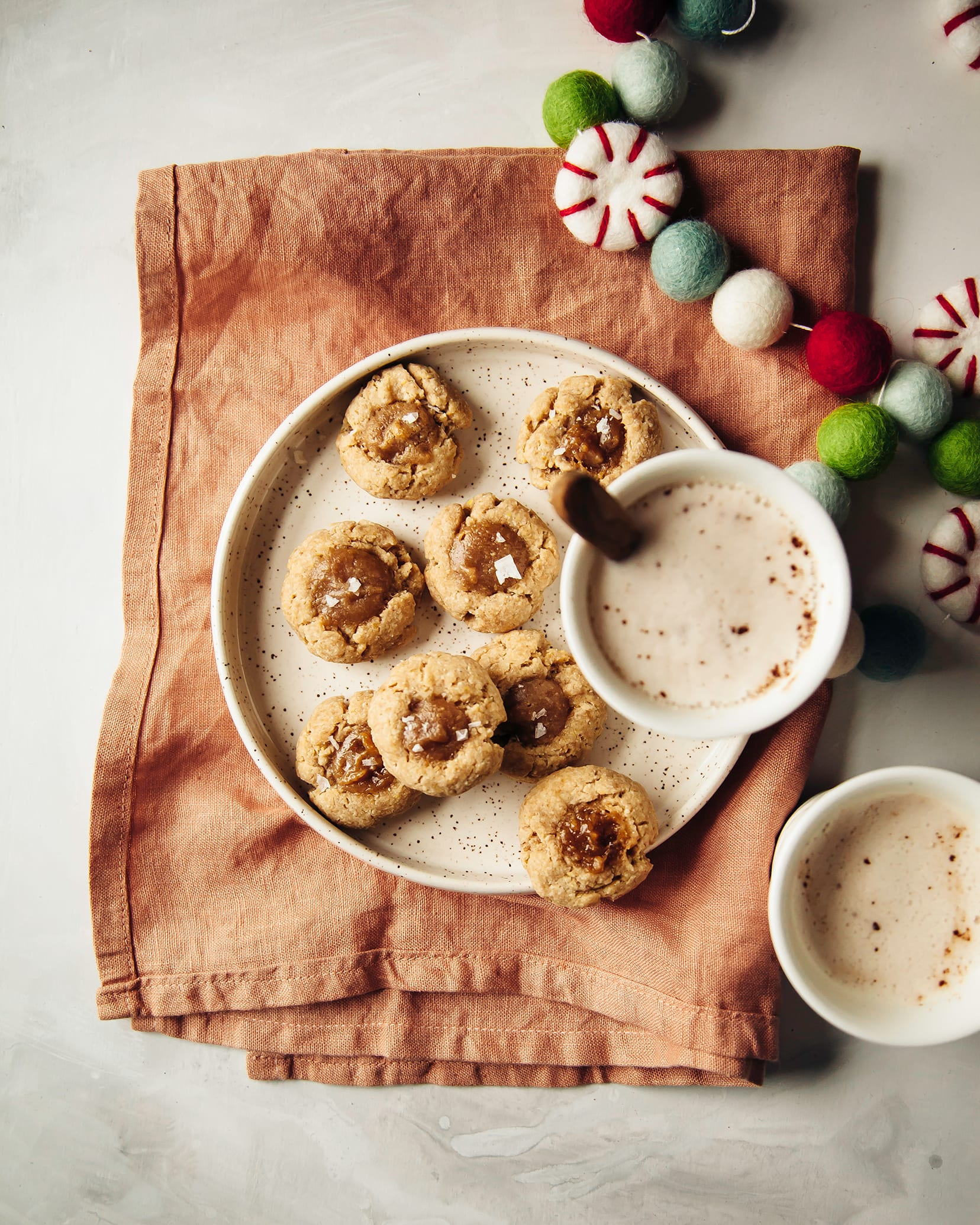 Overhead shot of cardamom thumbprint cookies with peanut butter caramel on a white speckled plate on top of a pink napkin. There are 2 cups of creamy coffee and a festive felt garland on the side.
