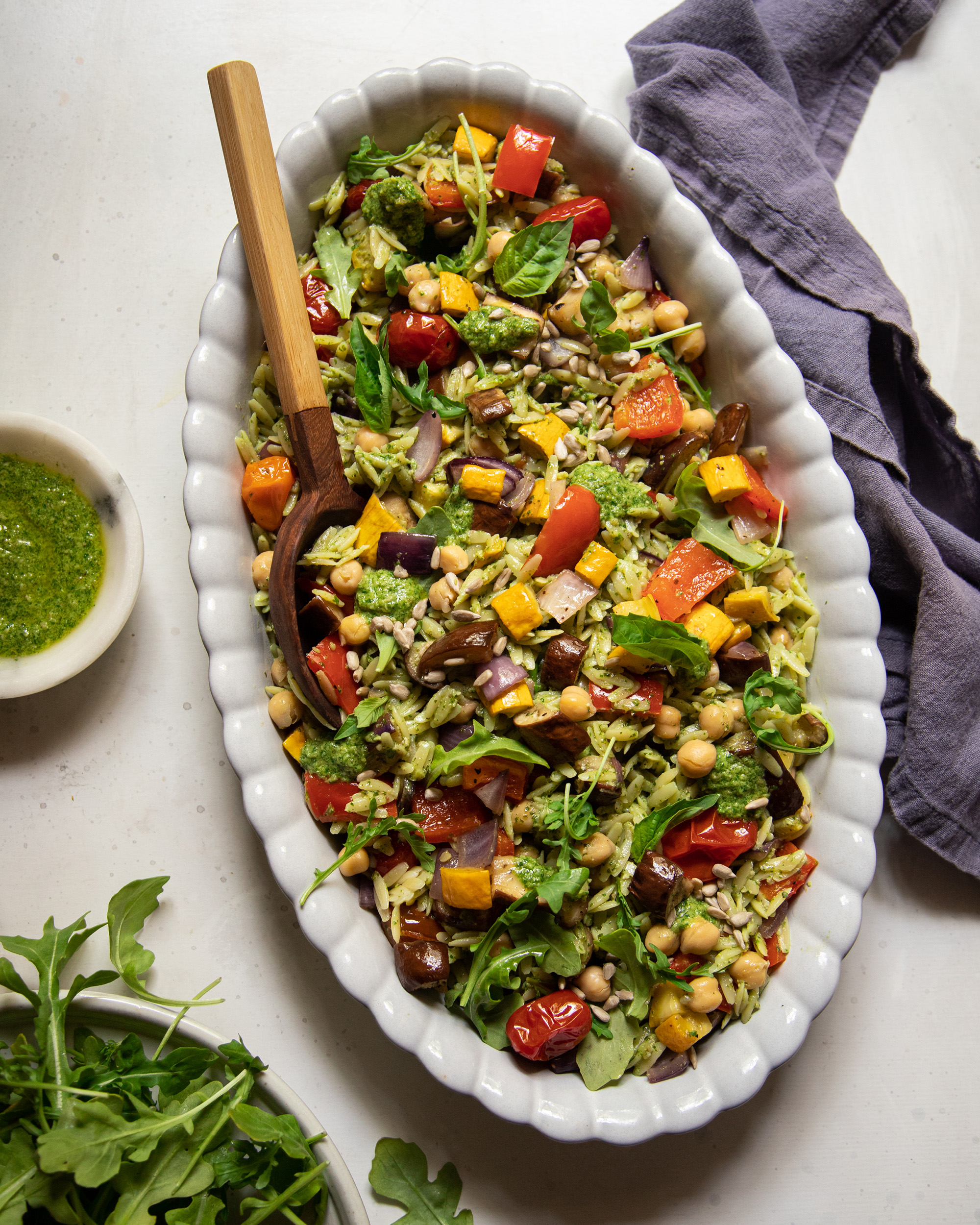 An overhead shot of a pesto orzo salad with dices of roasted vegetables and chickpeas. The dressing is creamy and bright green. There is a wooden spoon sticking out of the dish of salad.