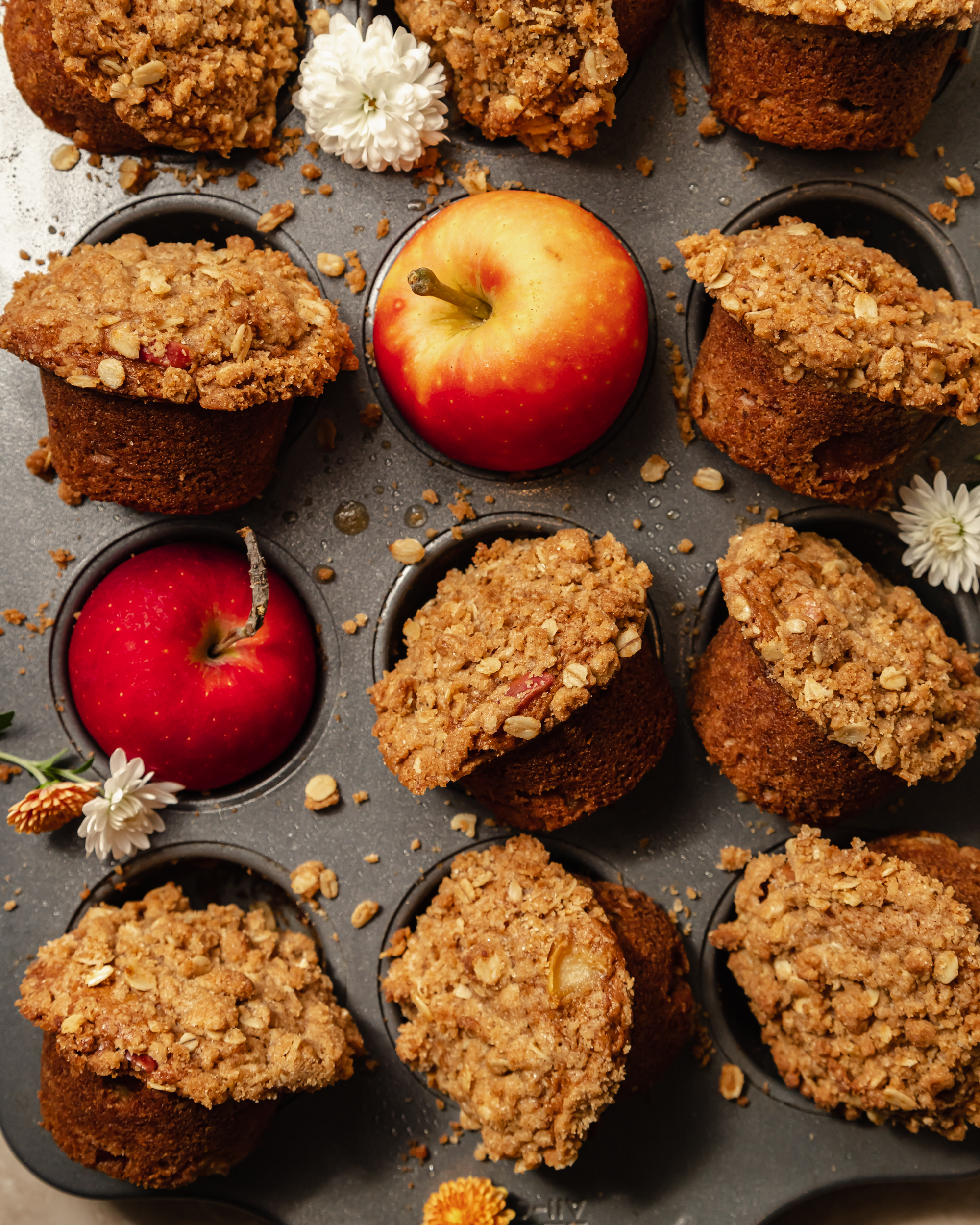 An overhead shot of baked vegan apple crisp muffins set upright in a muffin tin with apples in some of the muffin cups.