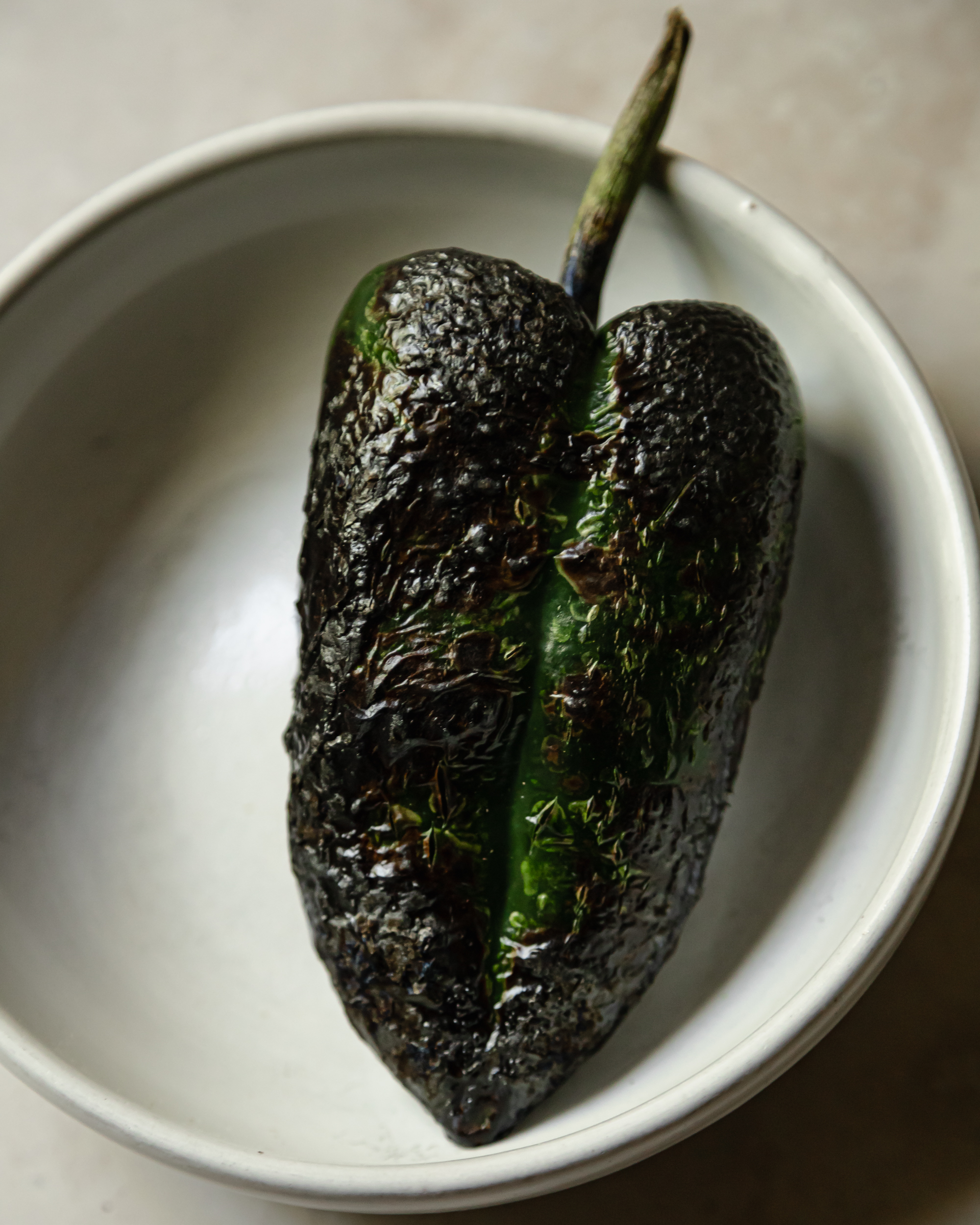 An up close shot of a charred poblano pepper in a white bowl.