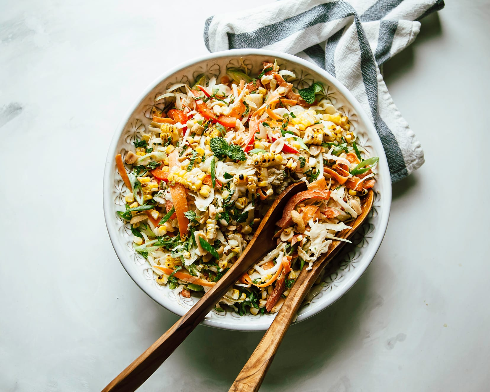 An overhead shot of charred corn slaw with peanut butter lime dressing. The slaw is served in a white patterned bowl on top of a white background with a striped napkin to the side.