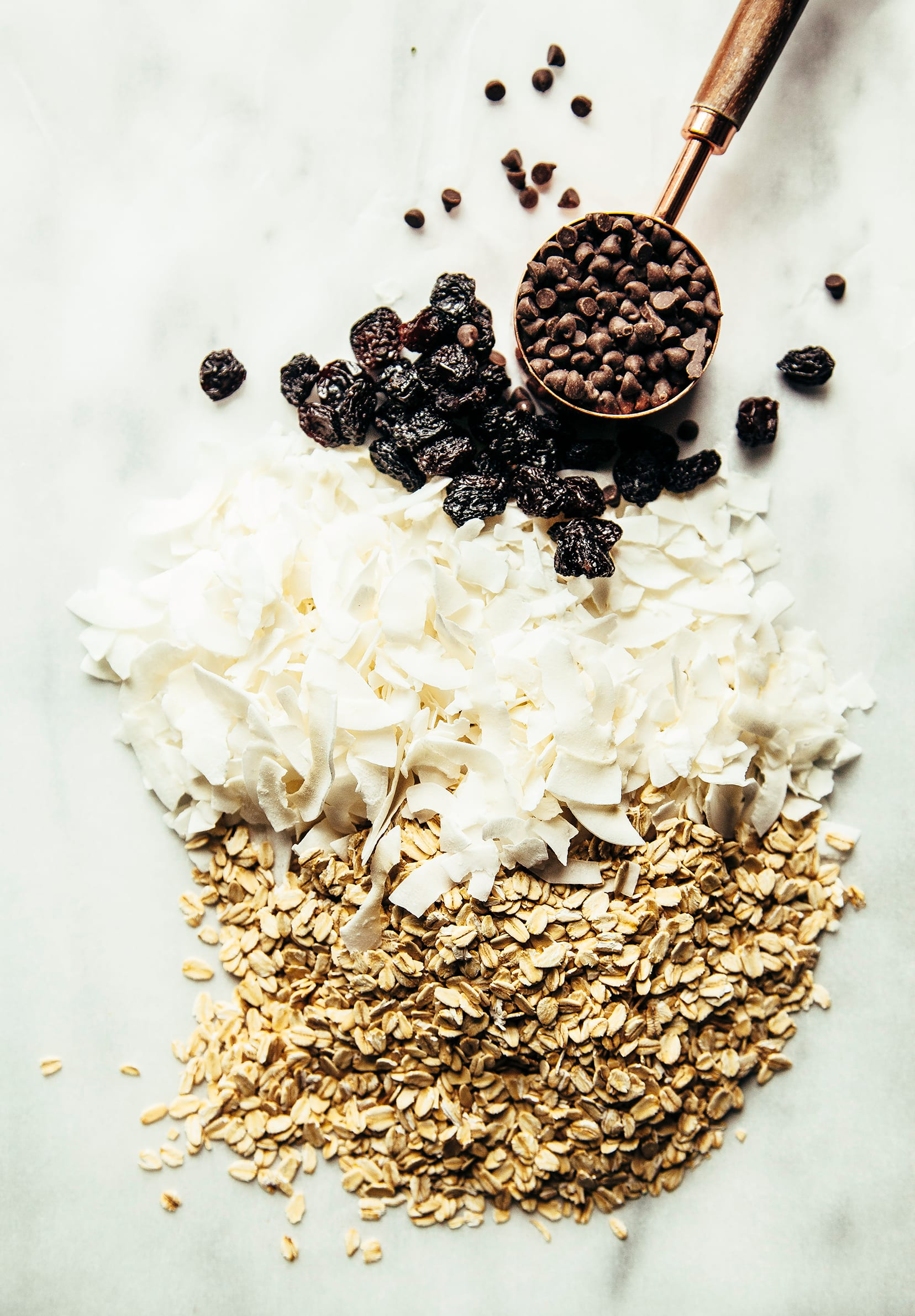 An overhead shot of chocolate chips, coconut flakes, raisins, and rolled oats, all lined up together.