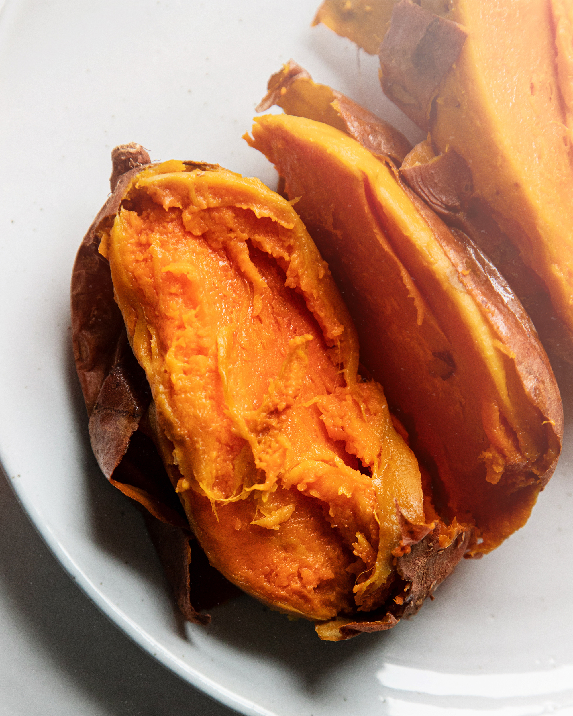 An up close, overhead shot of a split open baked sweet potato on a white plate.